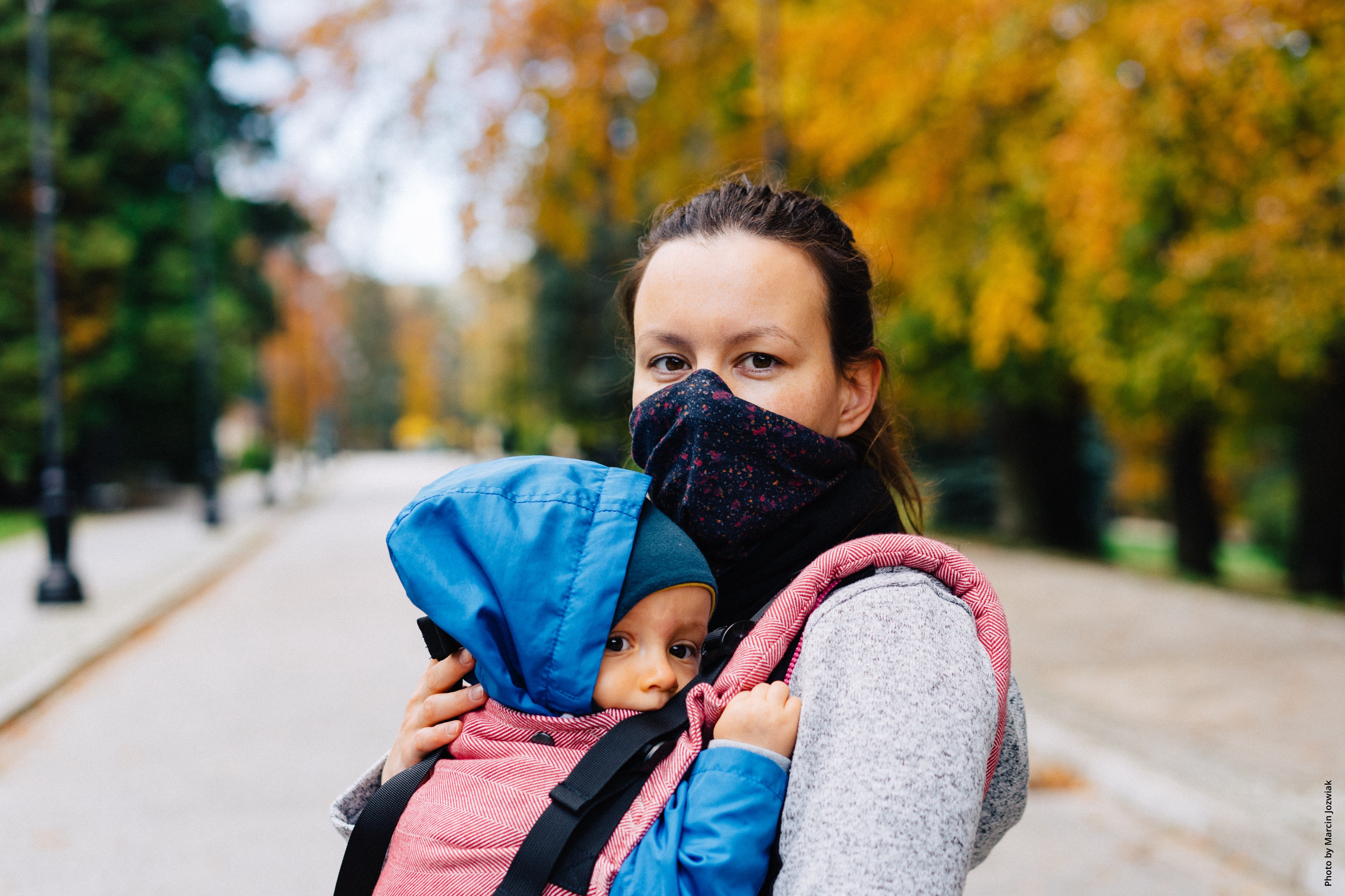 Young mother wearing COVID-19 protection mask holds her young child while crossing a street. Photo by Marcin Jozwiak.