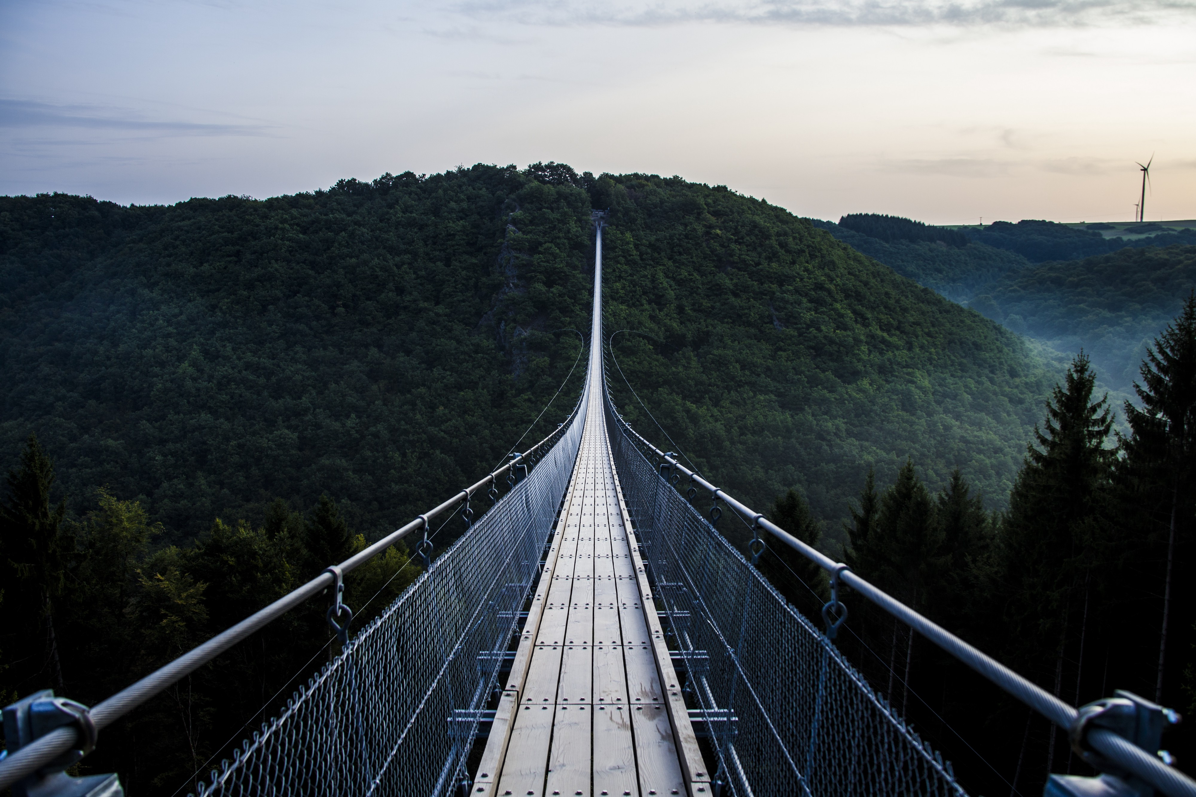 A very long bridge over a valley between two mountains.