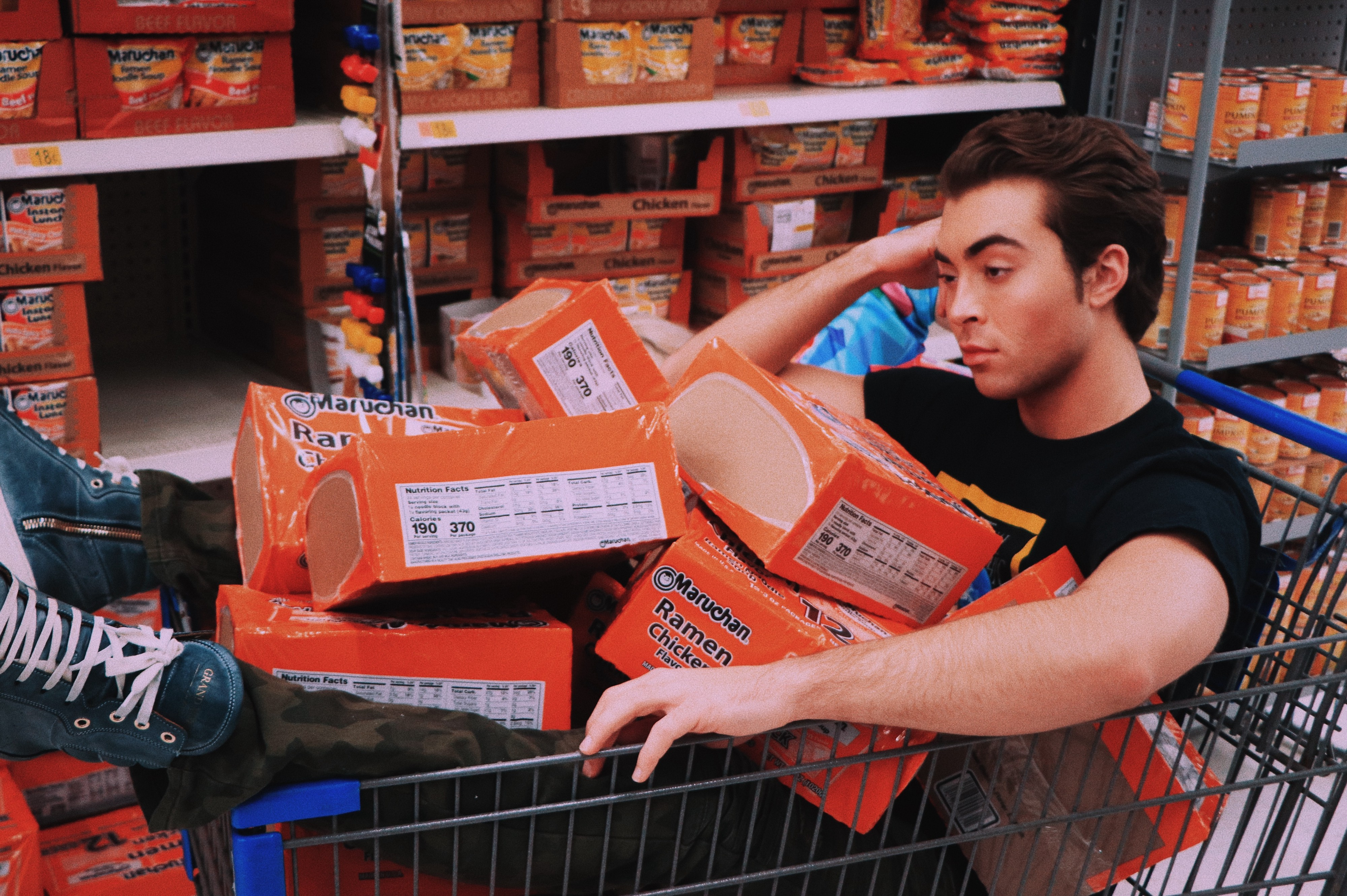 Young man in cart full of Ramen noodles
