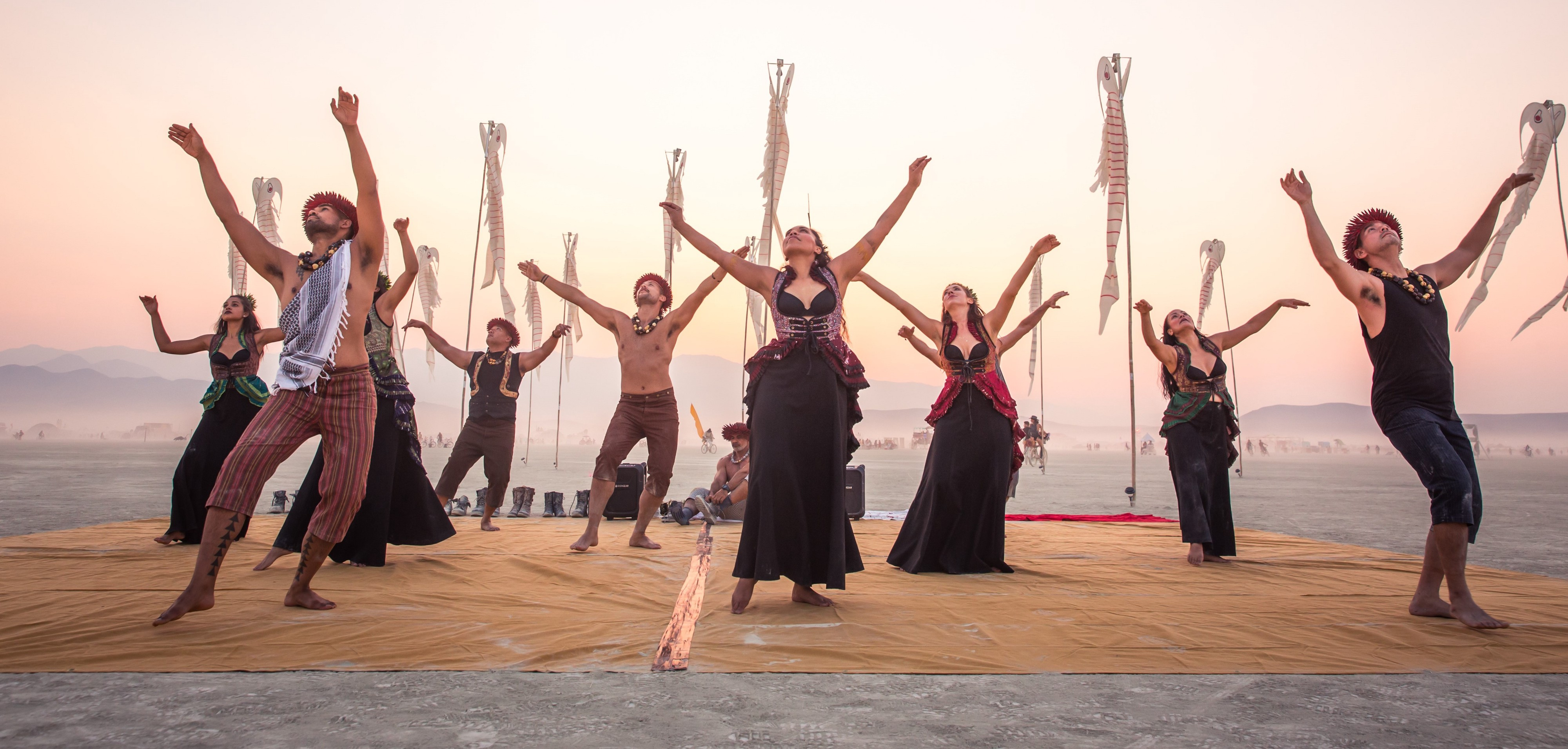 On a yellow fabric in the middle of the desert, hula performers stand with their arms raised in the air