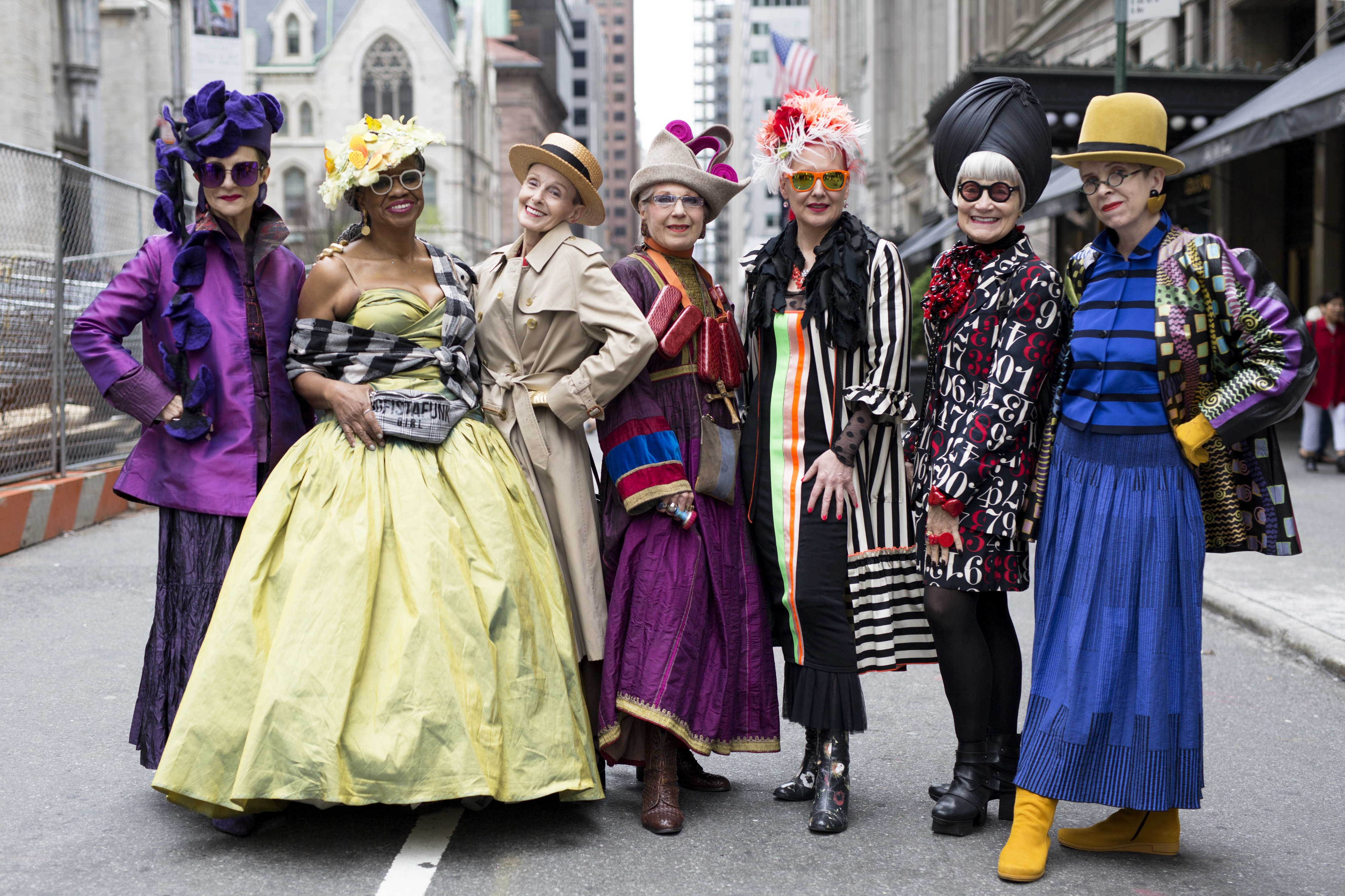 A group of older women wearing colorful, maximalist outfits in many colors and patterns with radiant expressions.