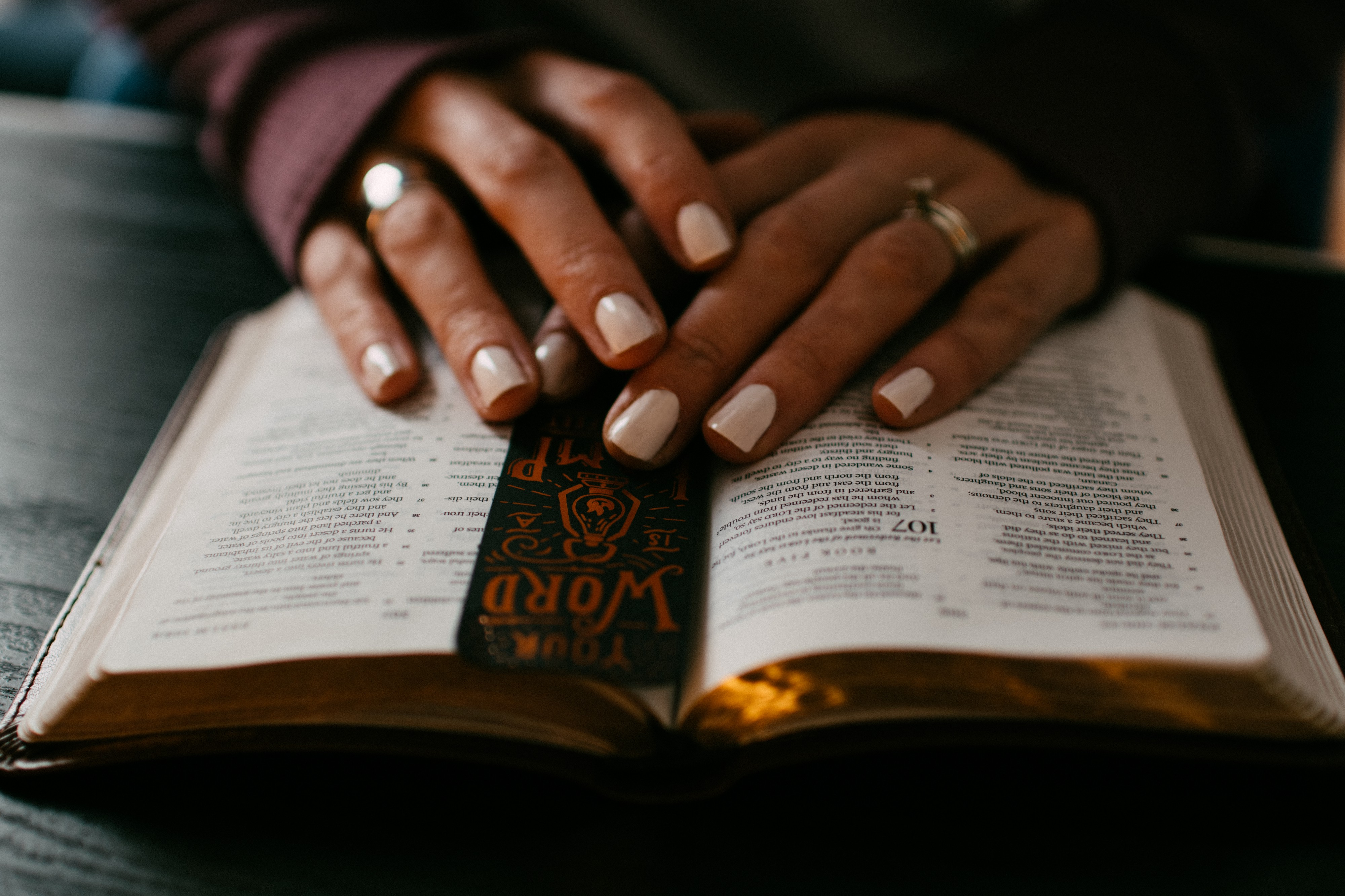 Woman's manicured hands on an open book with a black bookmark visible. Edges of pages are gold—colored. Woman wears rings.