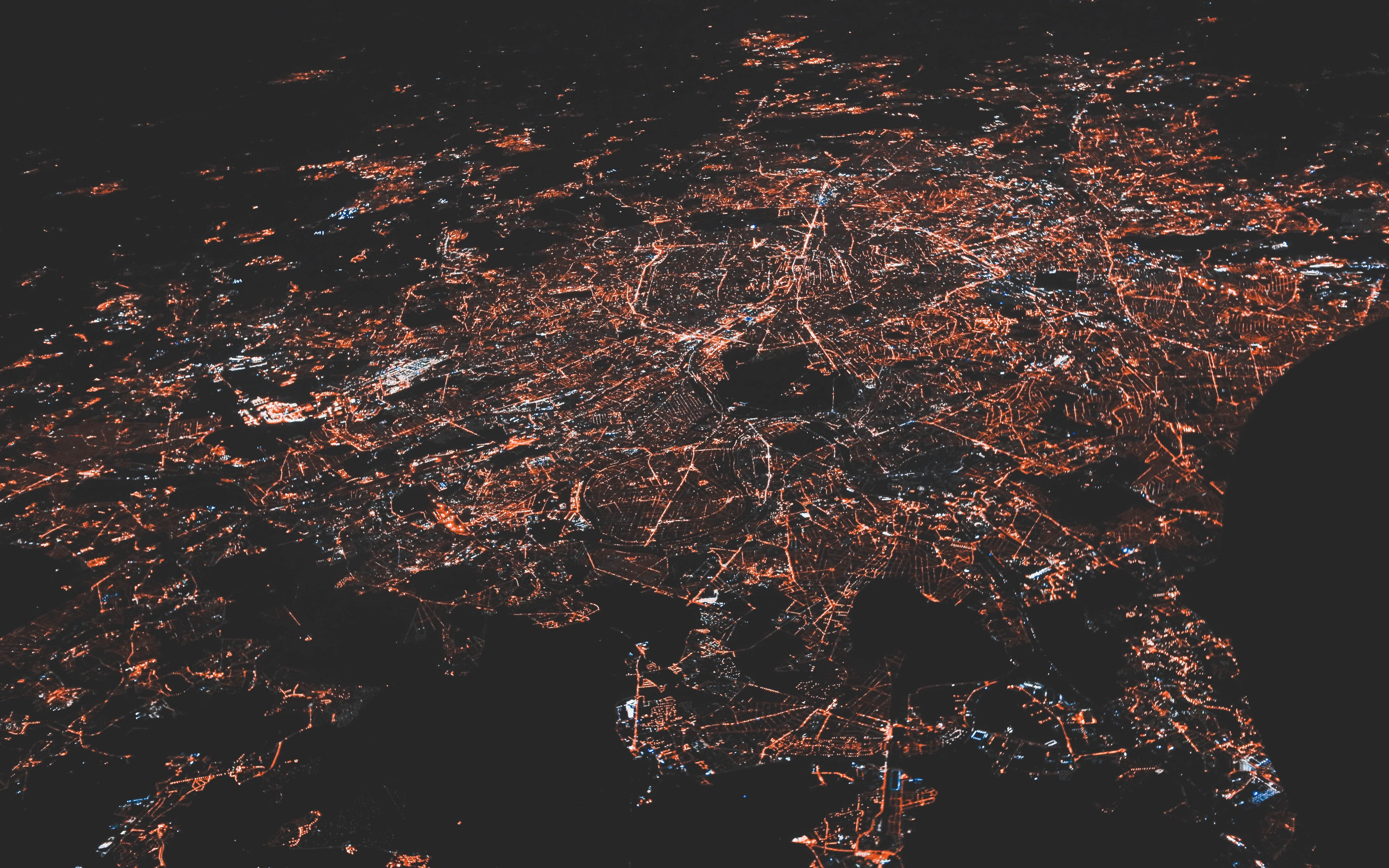 nighttime aerial photo of a city, streetlights and roads visible.