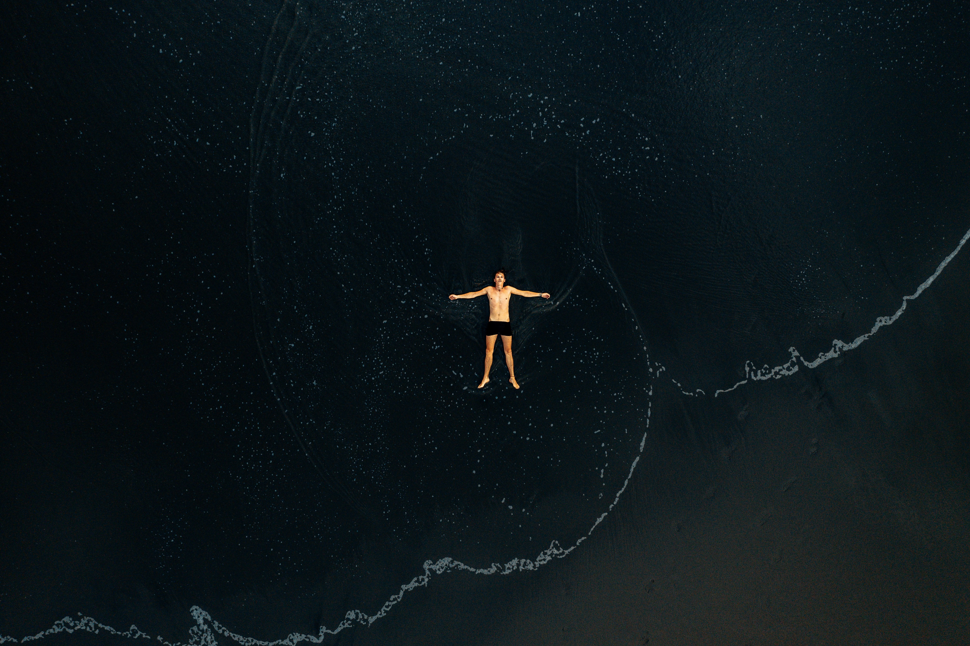 An aerial view of a person floating on their back in water but could almost be mistaken for floating in the vastness of space.