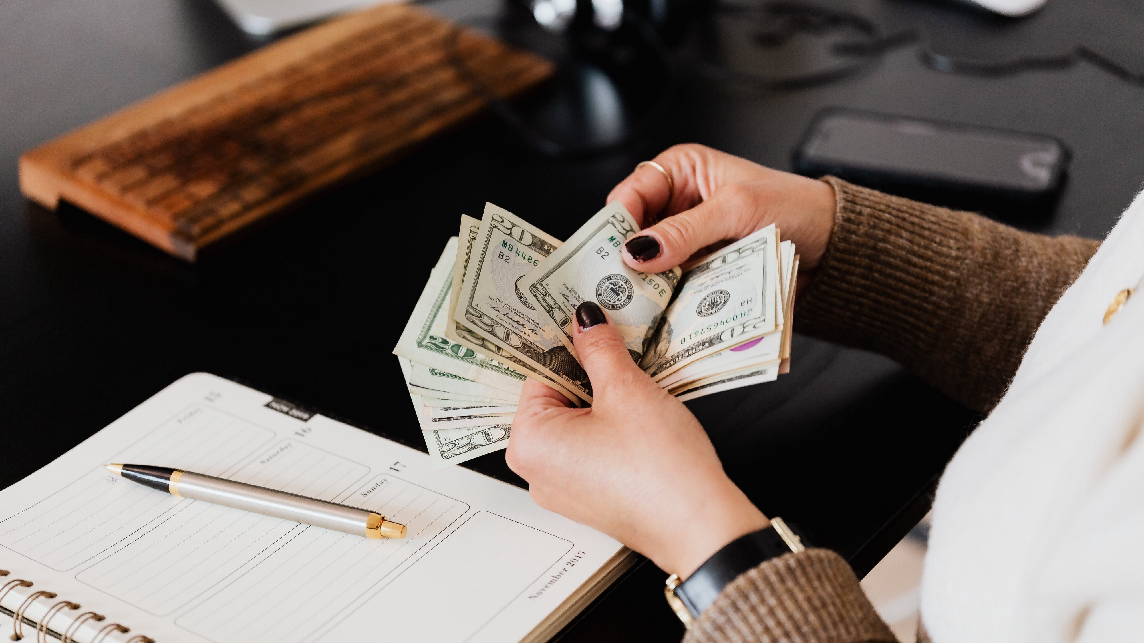 Womans hands holding a stack of $20 bills. A pen rests on top of a notebook on the desk in front of here.
