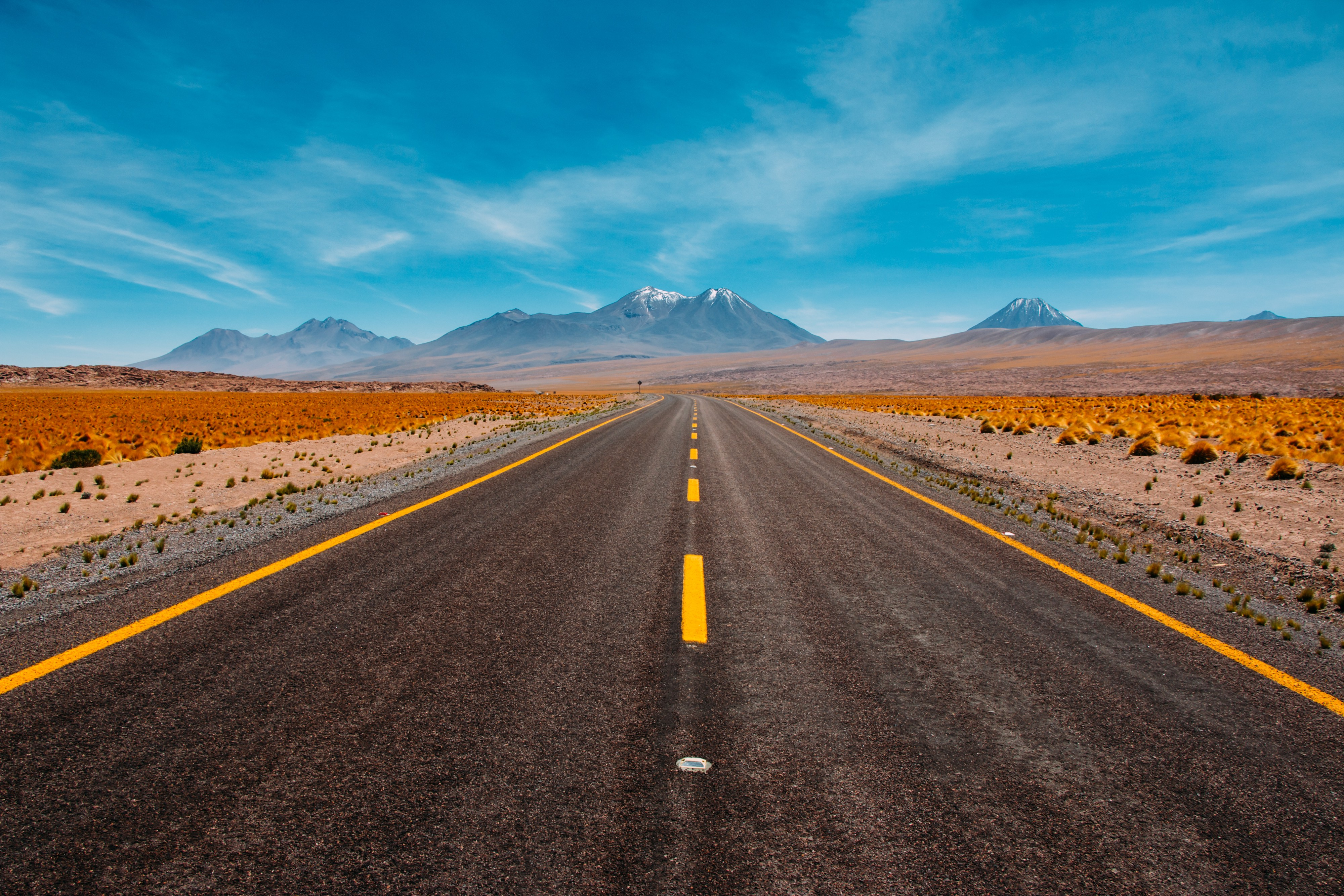 Photo of a straight long road leading into the far distance to low mountains