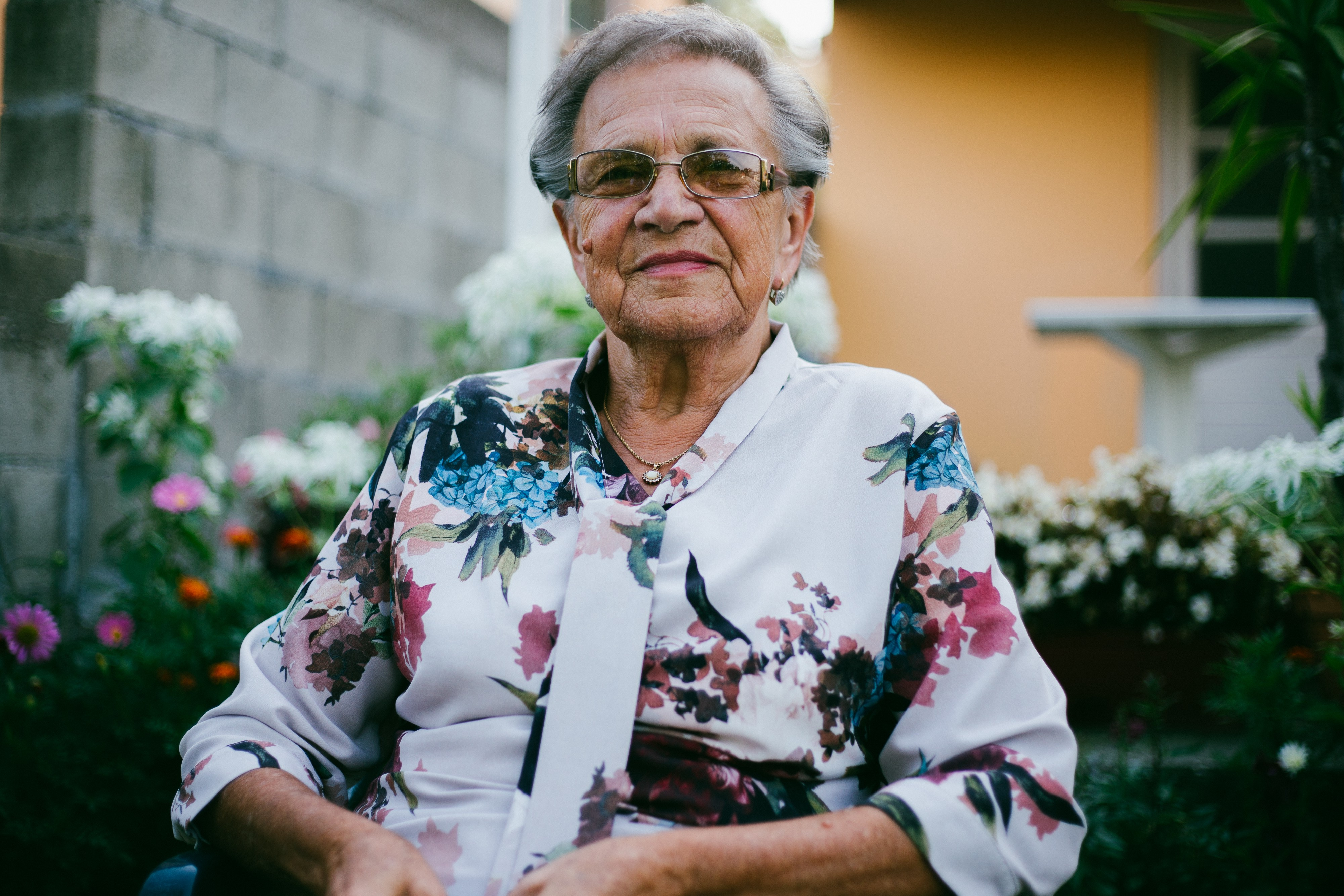 Content-looking grandma, with short hair, white blouse with flowery pattern, standing outside in a residential flower garden.