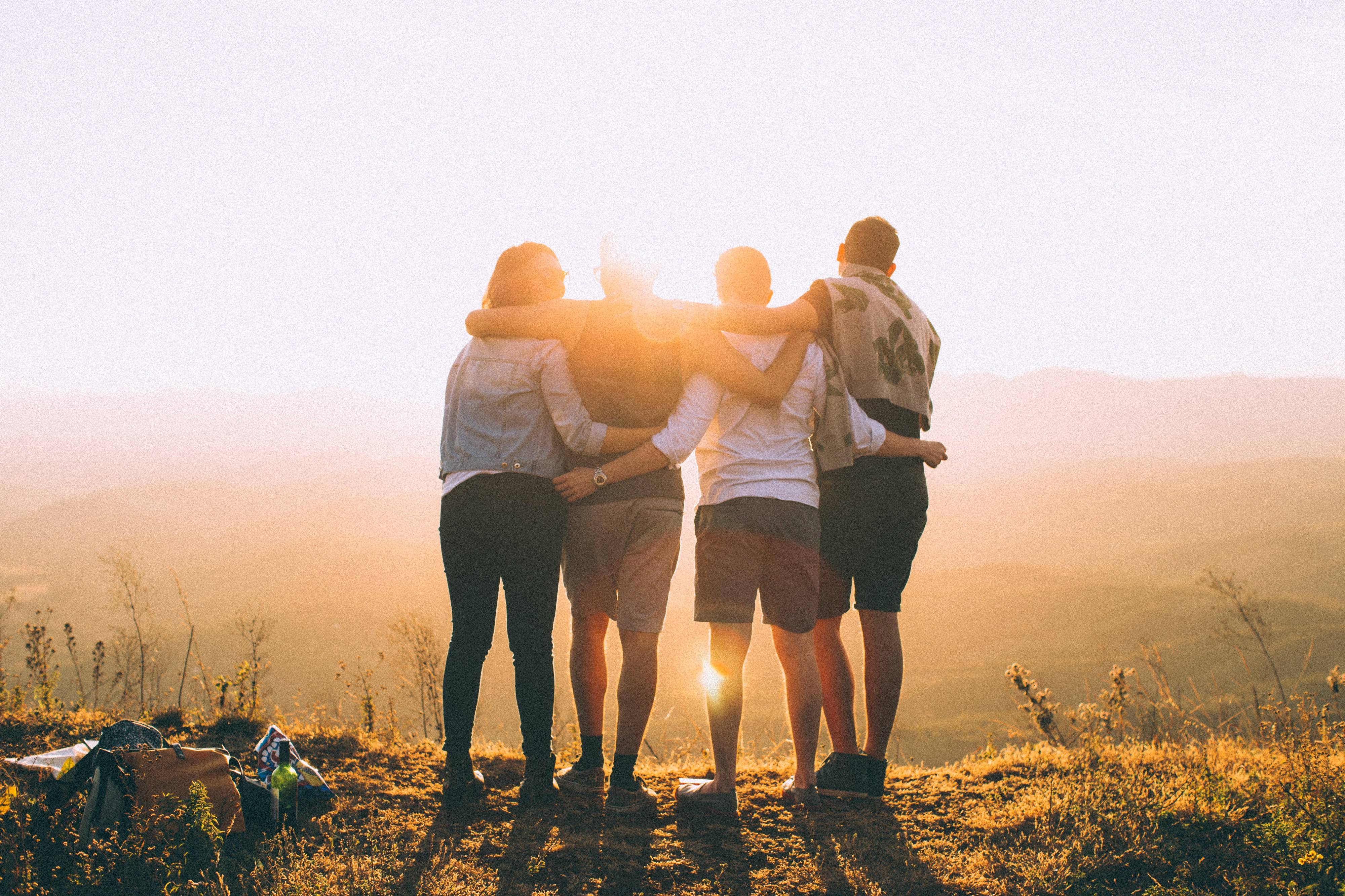 Four friends embrace on a mountaintop as the sun rises