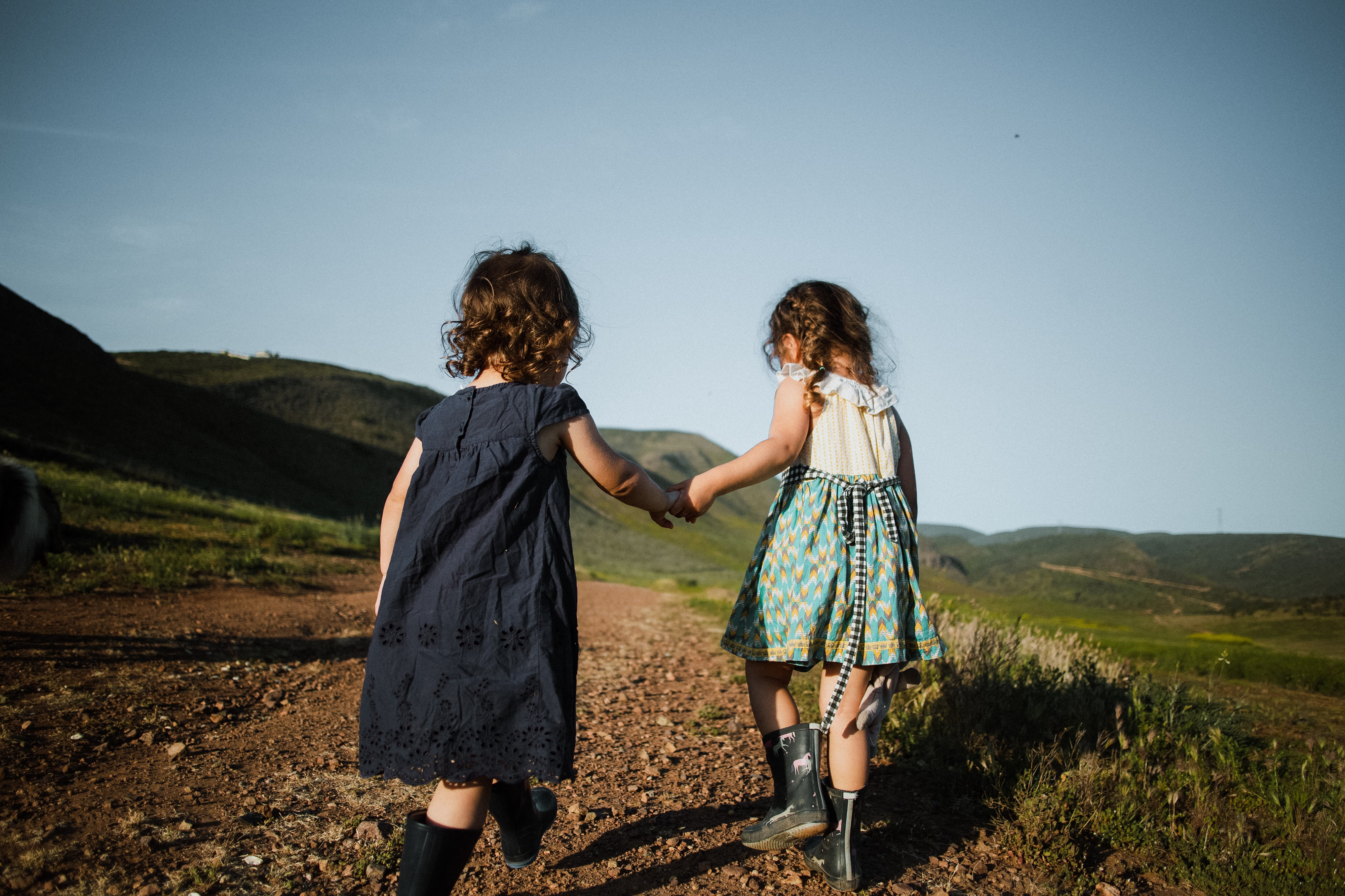 Two little girls (age around 3) holding hands while walking from the camera surrounded by open plains and nature.