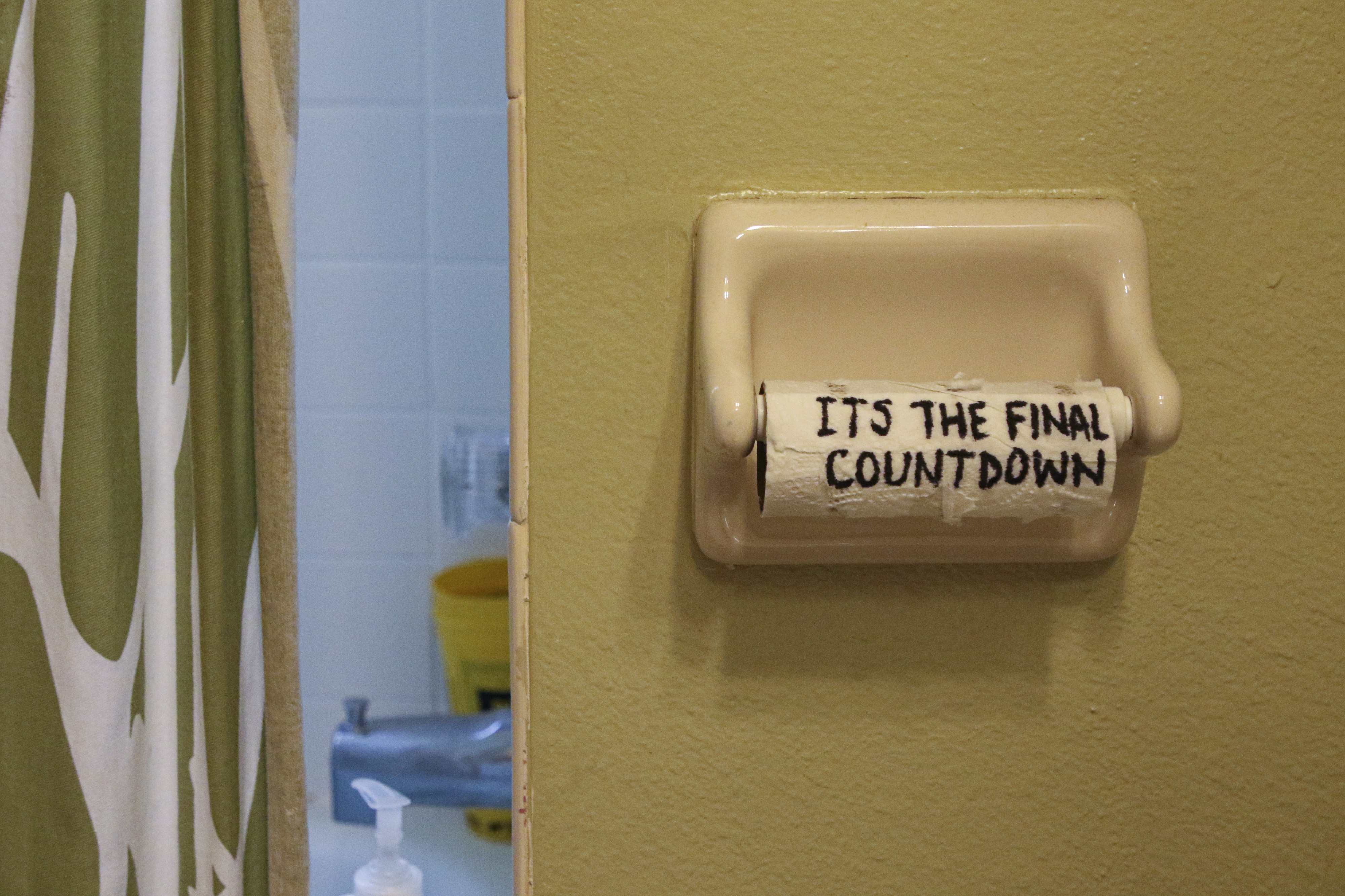 Empty toilet paper roll with the words, it's the final countdown, written on it in black sharpie.
