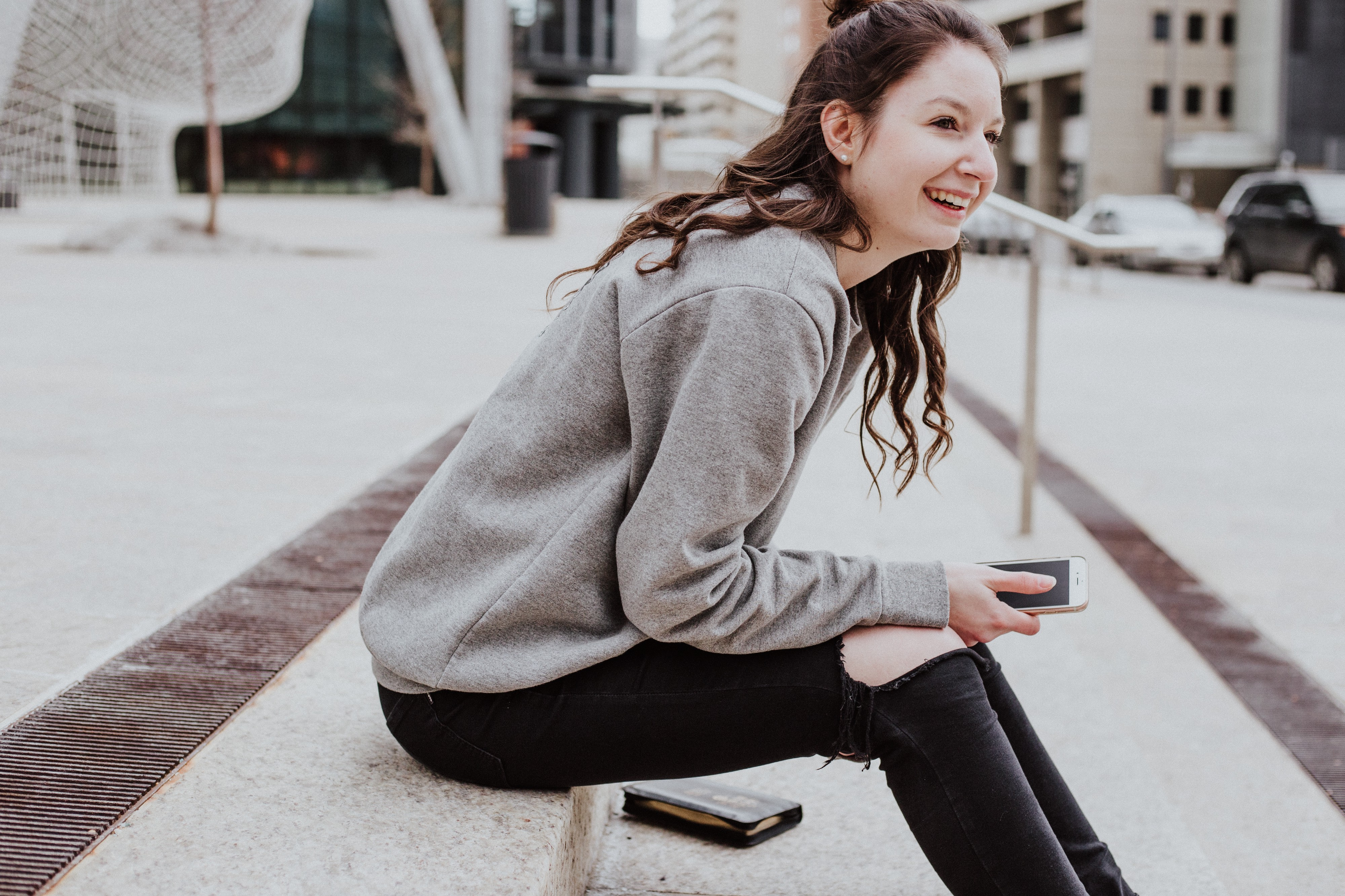 Freelance writer lady in gray sweatshirt and black jeans smiling as she sits on steps outside with a phone in her hand.