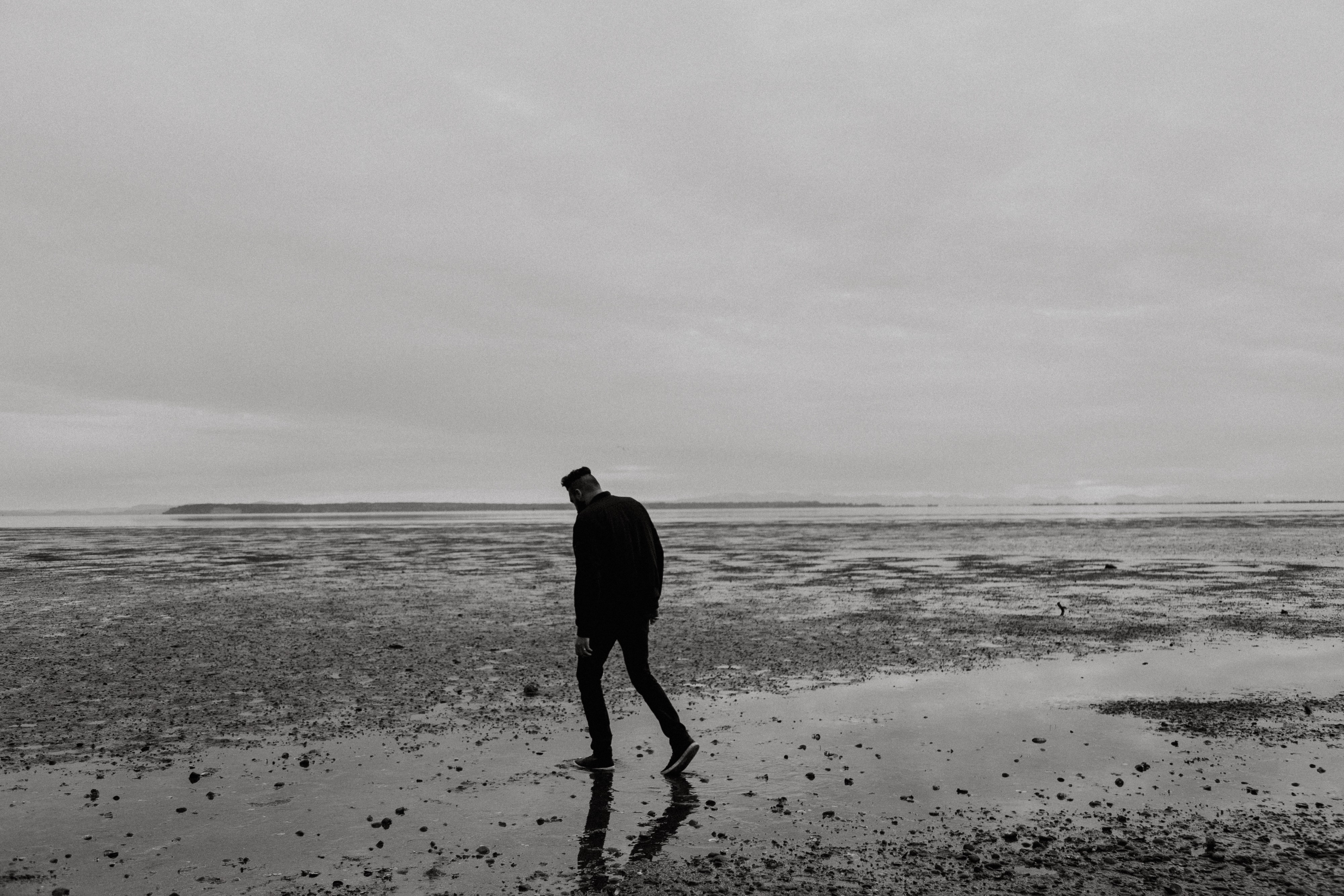 Man walking alone on a beach with his head down in sadness
