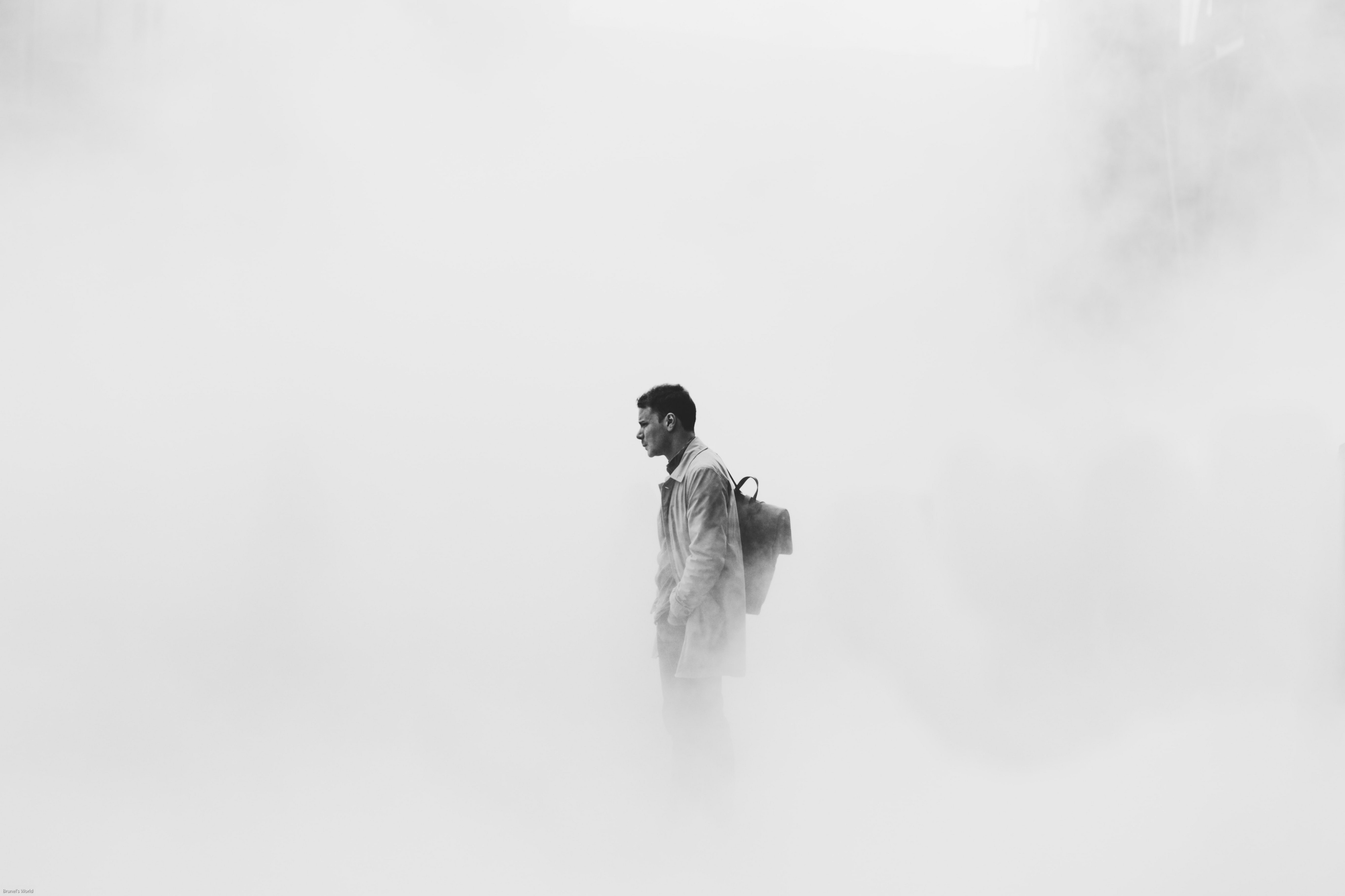 black and white photo of man wearing backpack standing in a cloudy misty space