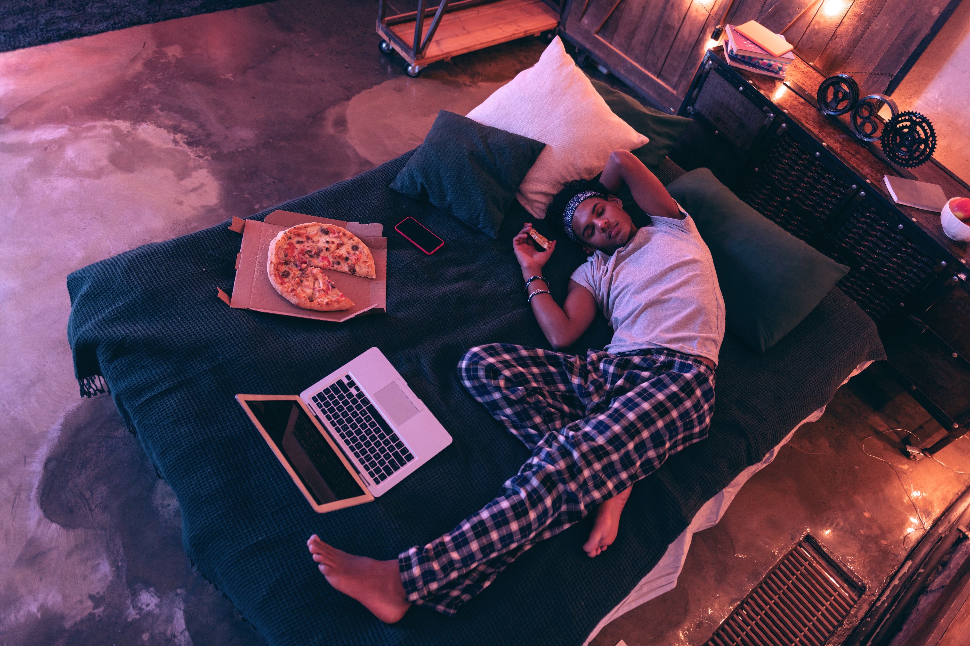 A young guy in checkered pajama trousers falling asleep with a slice of pizza in his hand in bed next to a pizza box and open laptop. He has the itis.