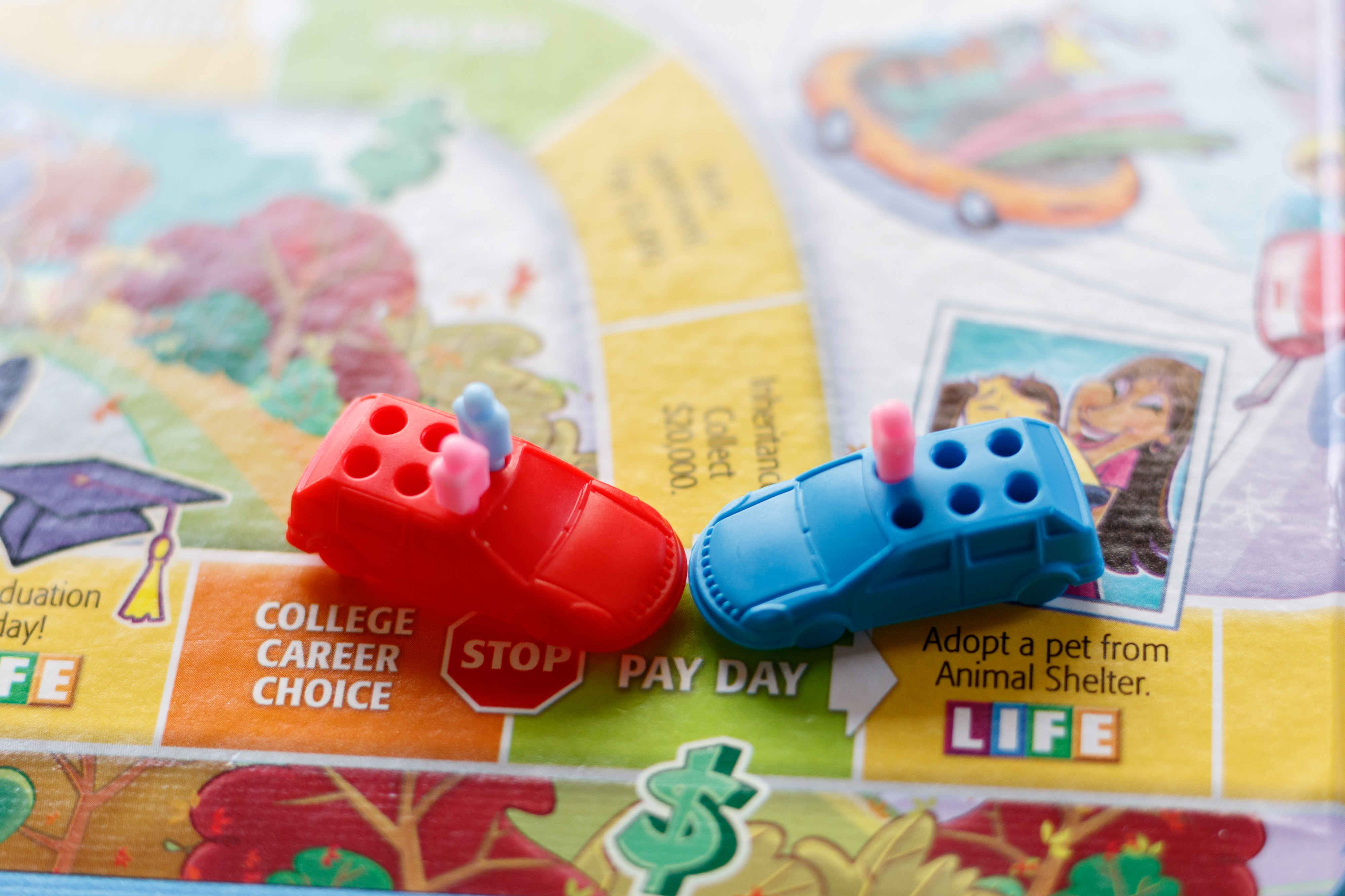 Photo depicting a car crash using the board and game pieces from The Game of Life
