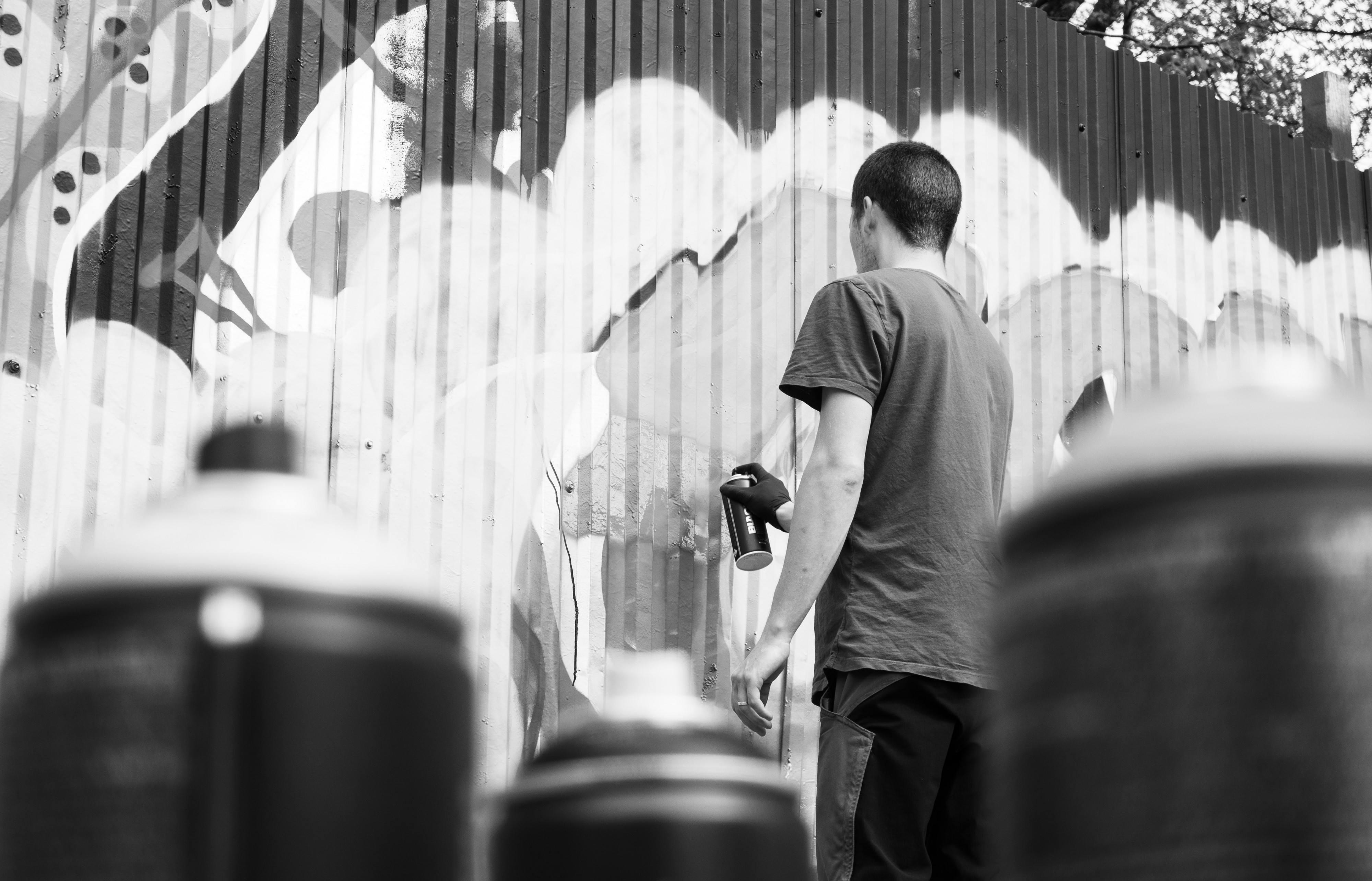 Photograph of a man spray painting a wall