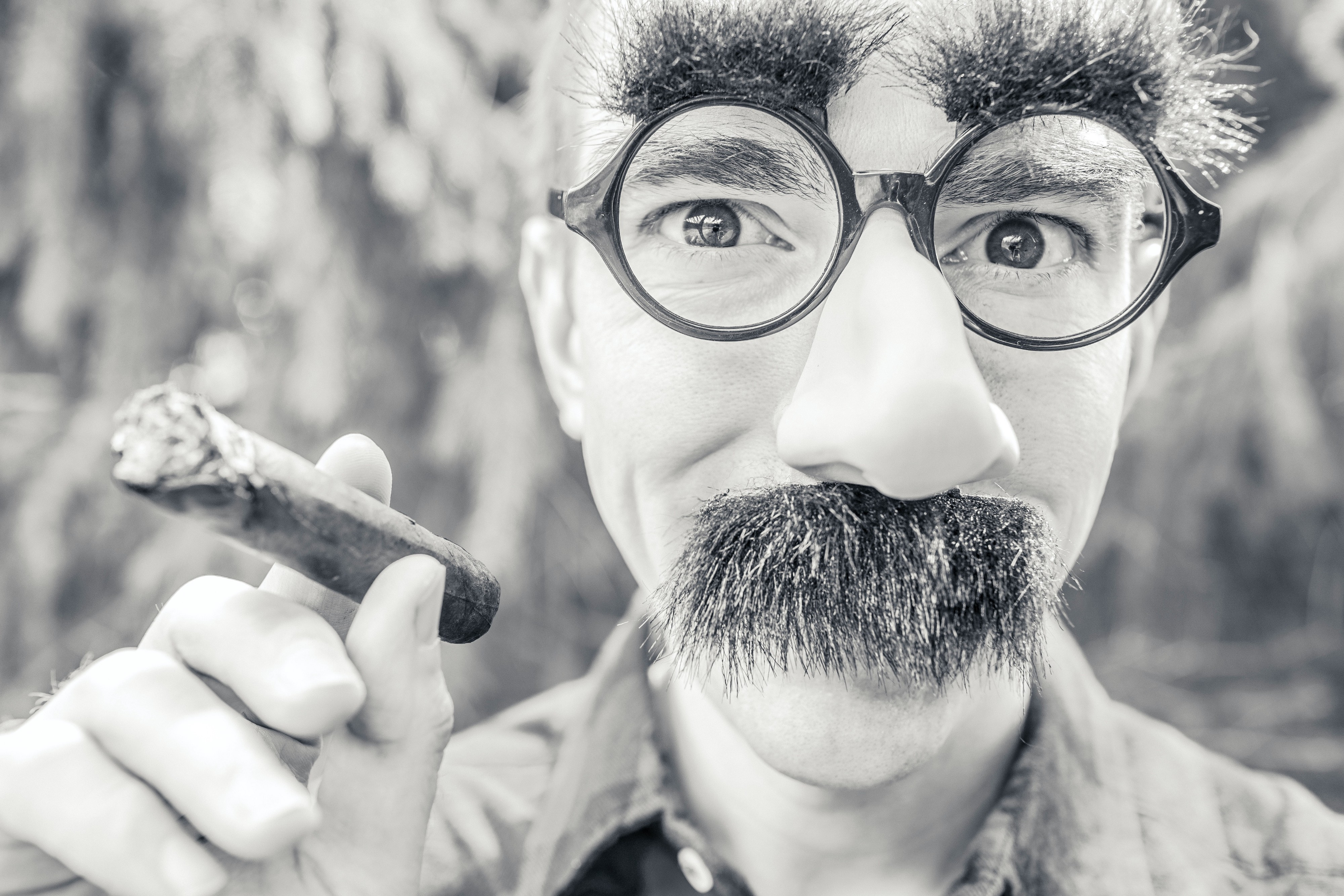 Guy trying to be funny by wearing Grouch Marx looking glasses and mustache.
