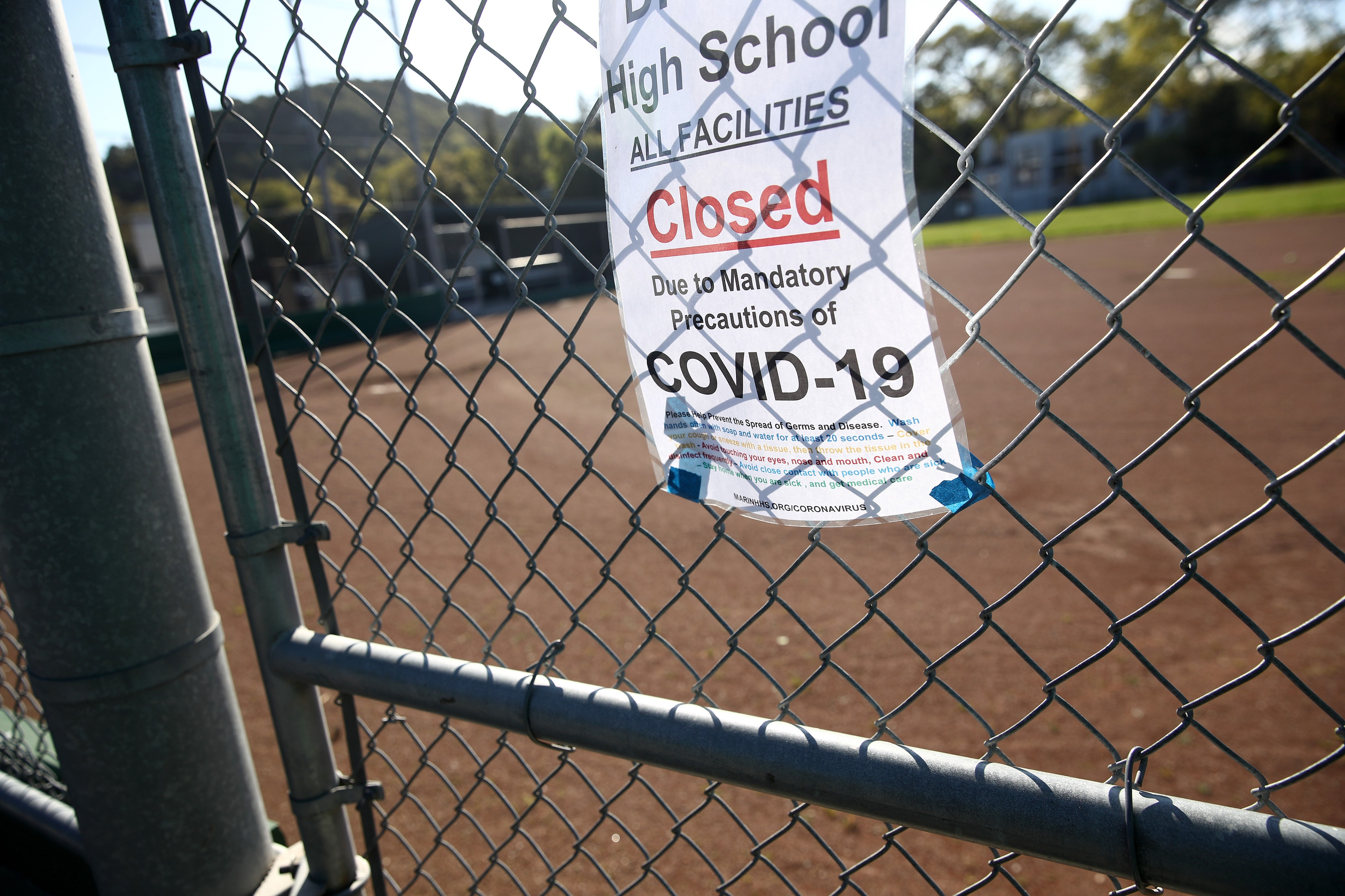 """Sign taped to chain linked fence that reads """"High School and Facilities Closed Due to Mandatory Precautions of COVID-19."""""""