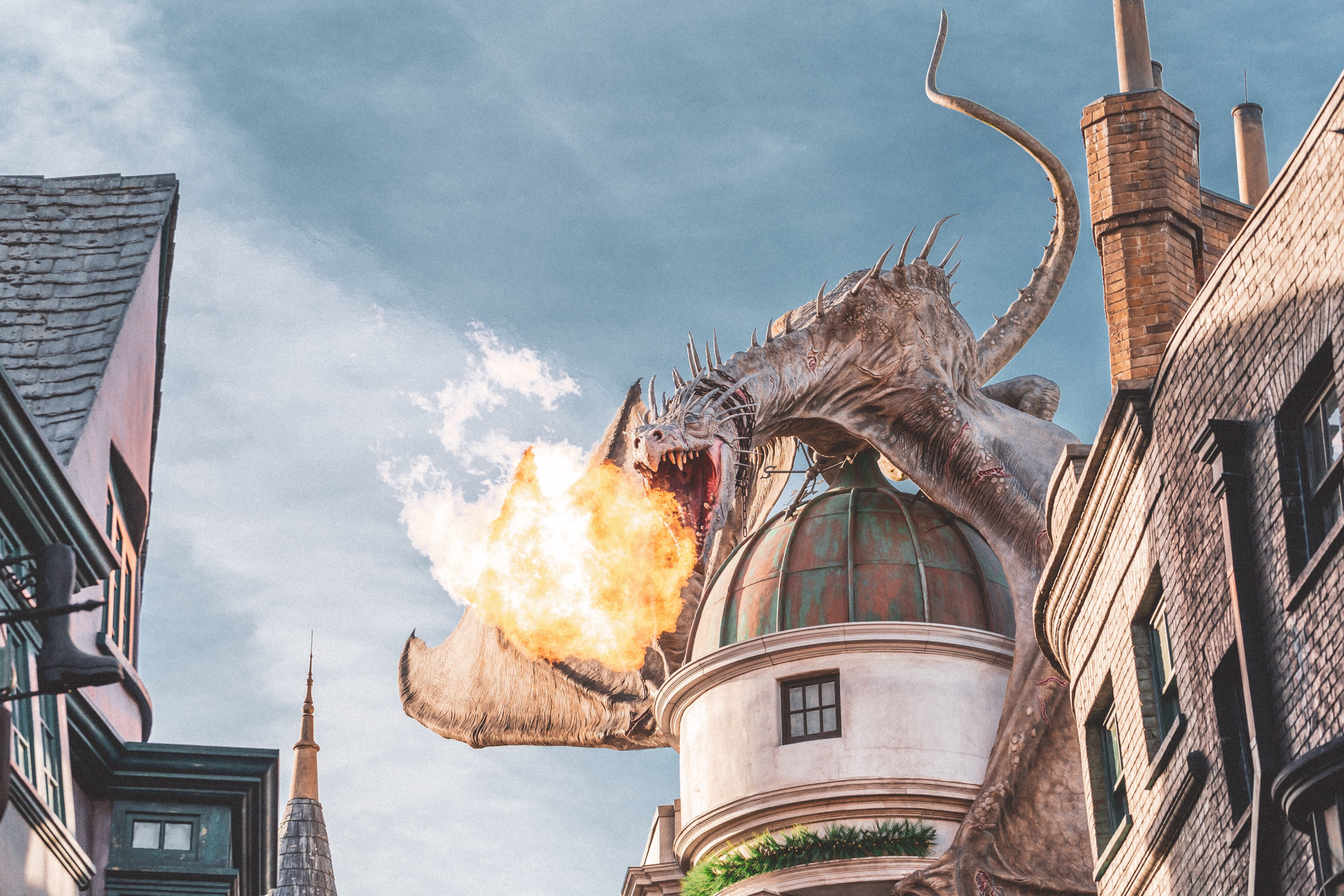 A dragon on top of a domed building breathing fire across a village