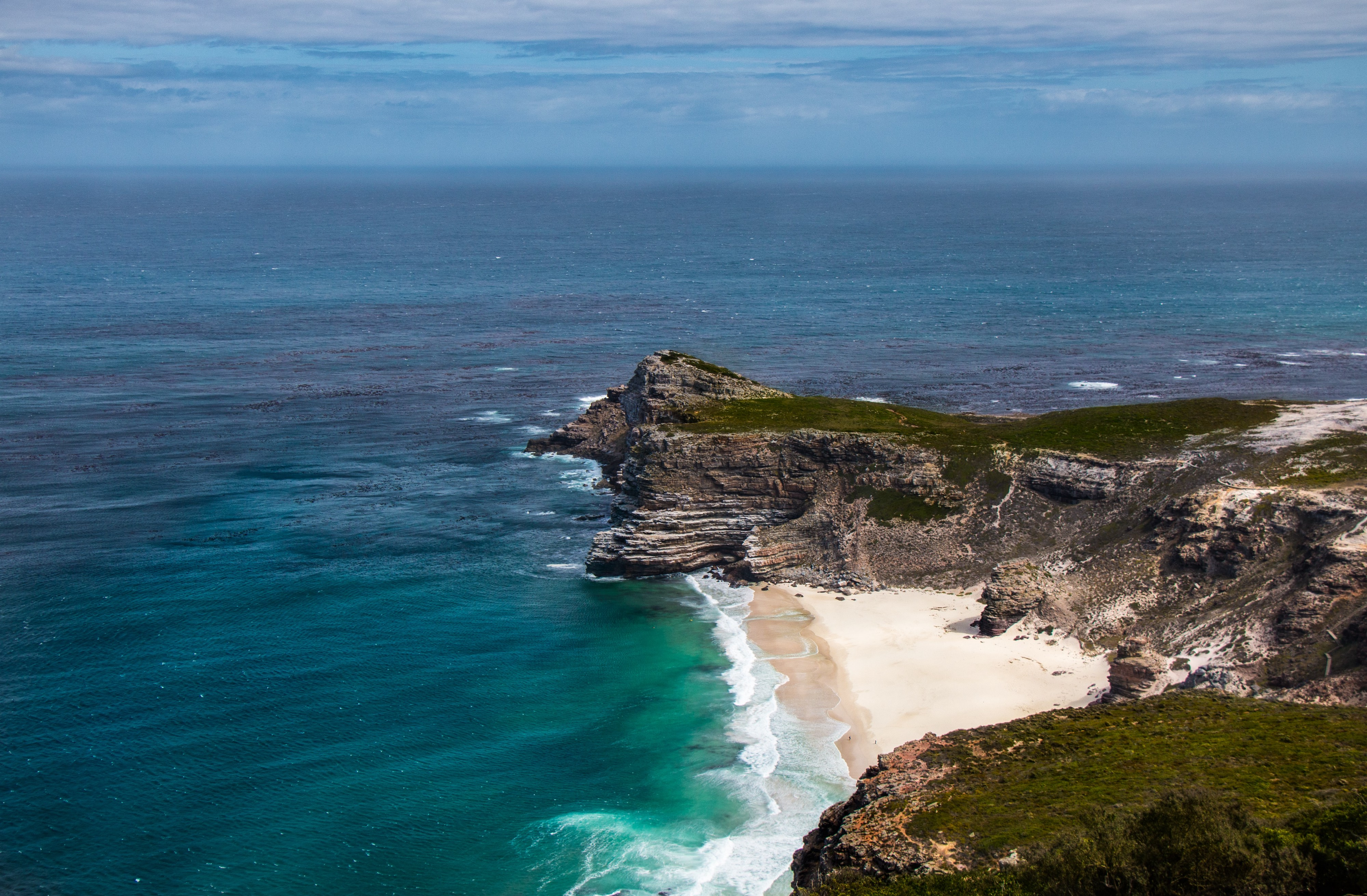Green mountain cliff and sandy edge of the Cape of Good Hope poking out into a blue green ocean.
