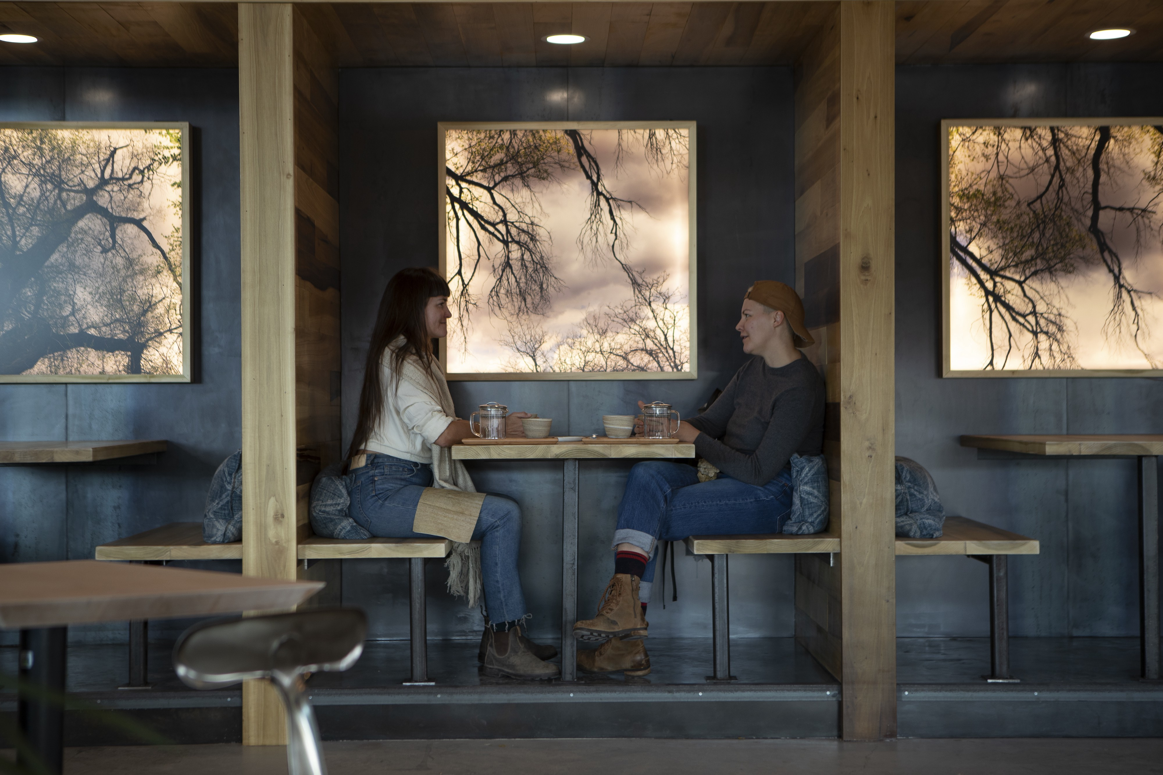 Two individuals sit at a wooden booth