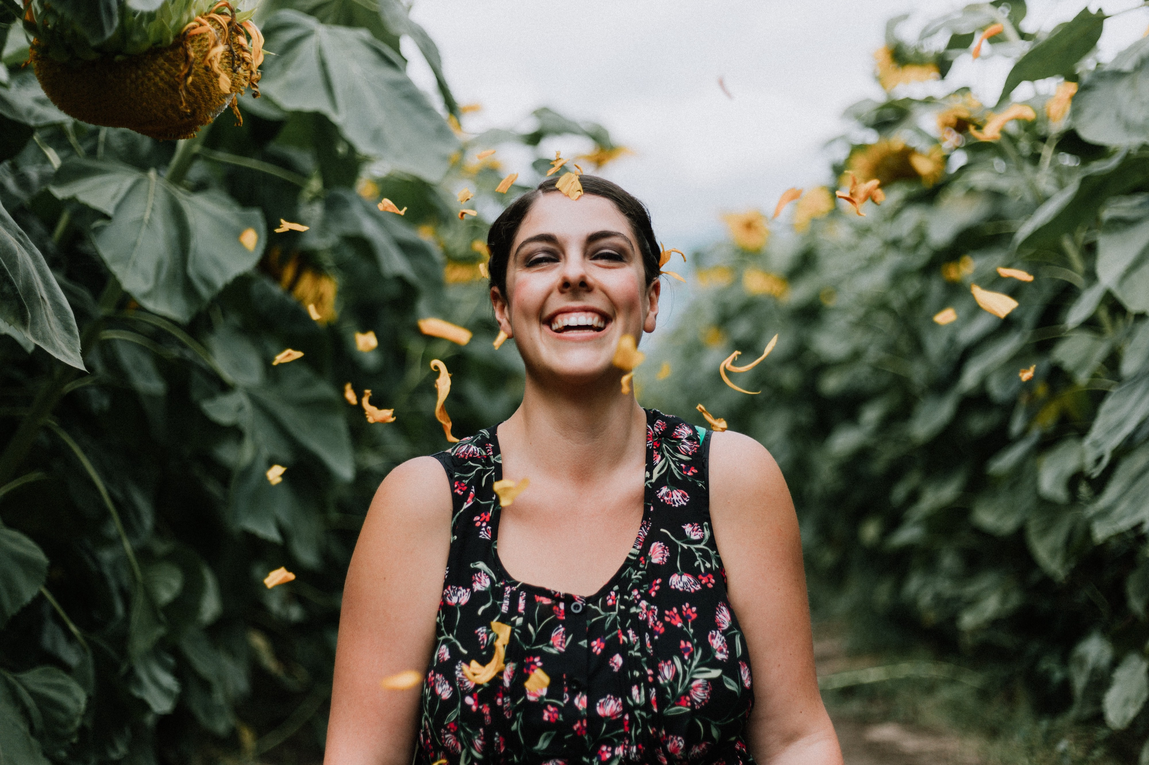 smiling woman with brown hair in flowered dress standing in middle of sunflower field