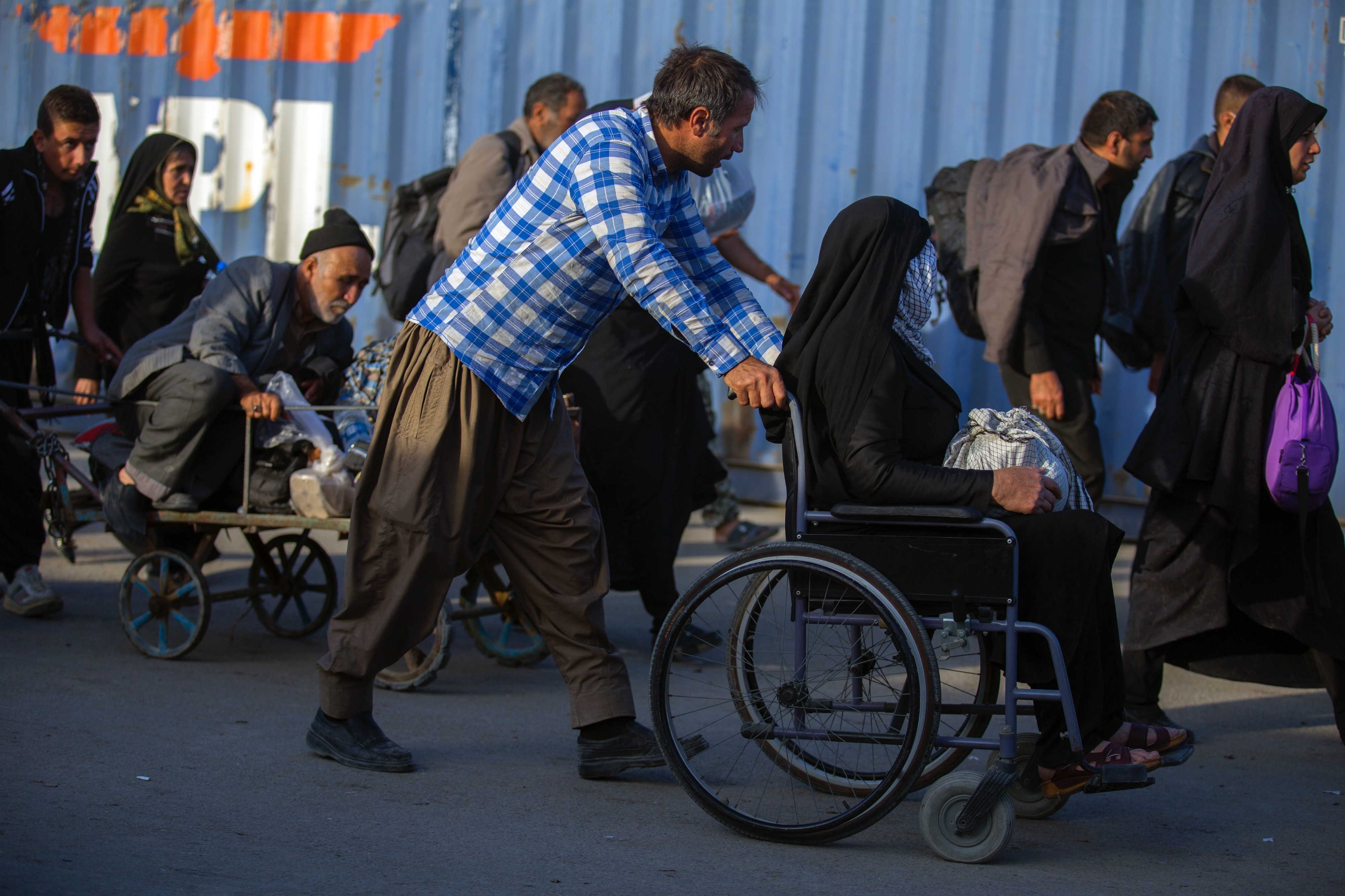 Middle Eastern man pushing woman dressed in an abaya in a wheelchair in crowded city setting