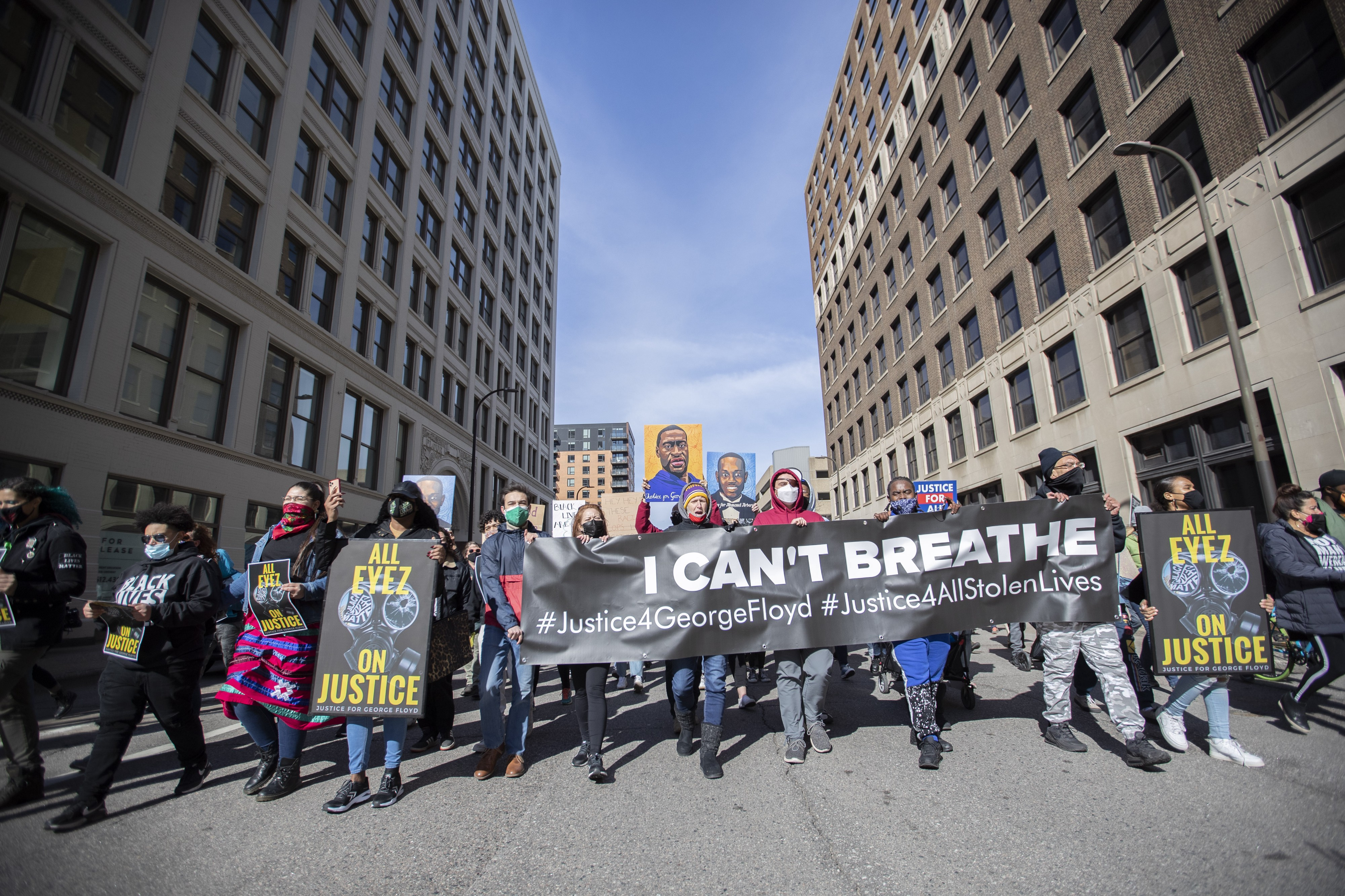 "Protestors hold signs saying ""I can't breathe"" and ""All Eyez on Justice"""