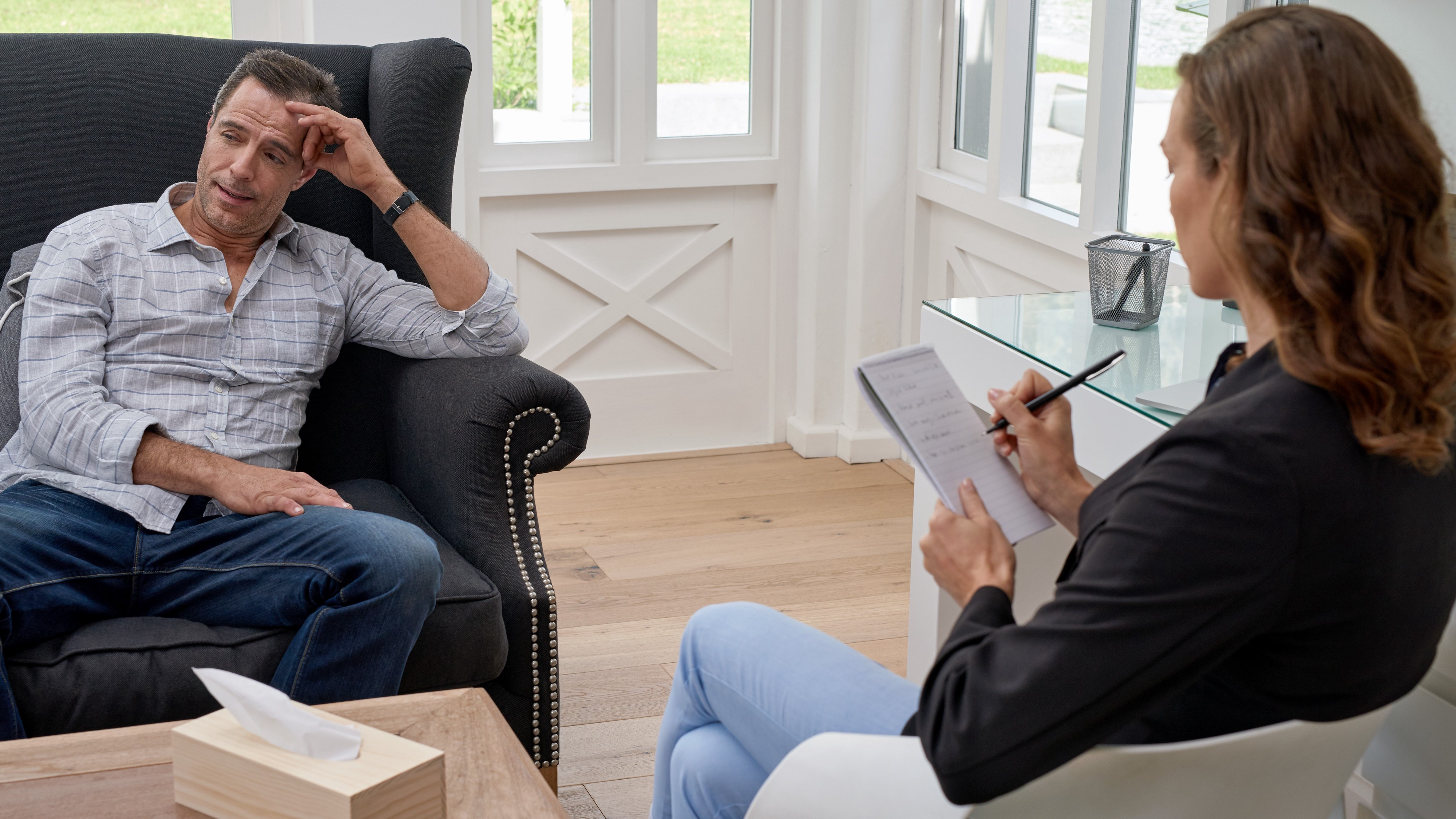 Middle-aged man sitting with female therapist