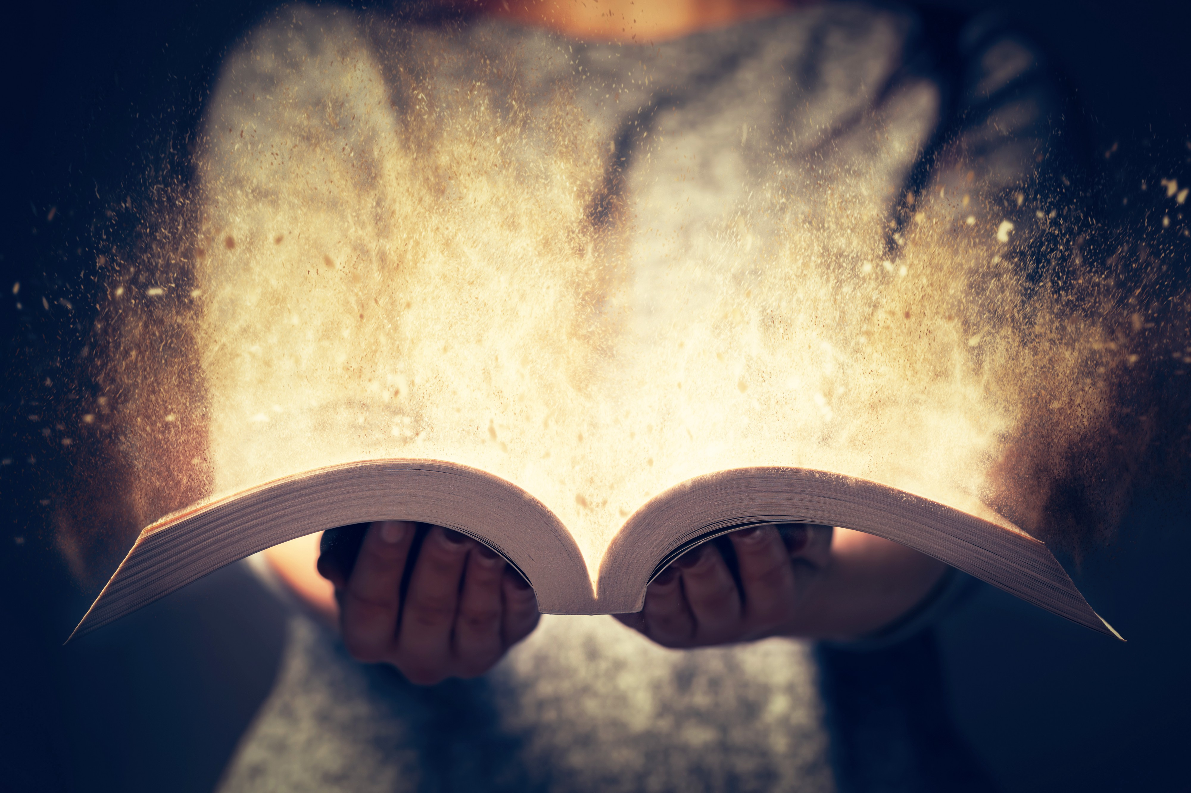 Woman holding a book that sparks light