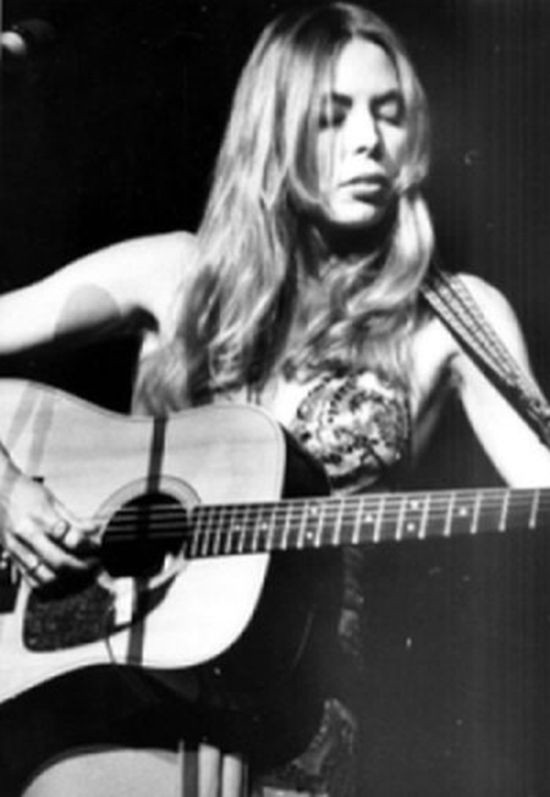 Joni Mitchell, playing an acoustic guitar at a concert in 1974