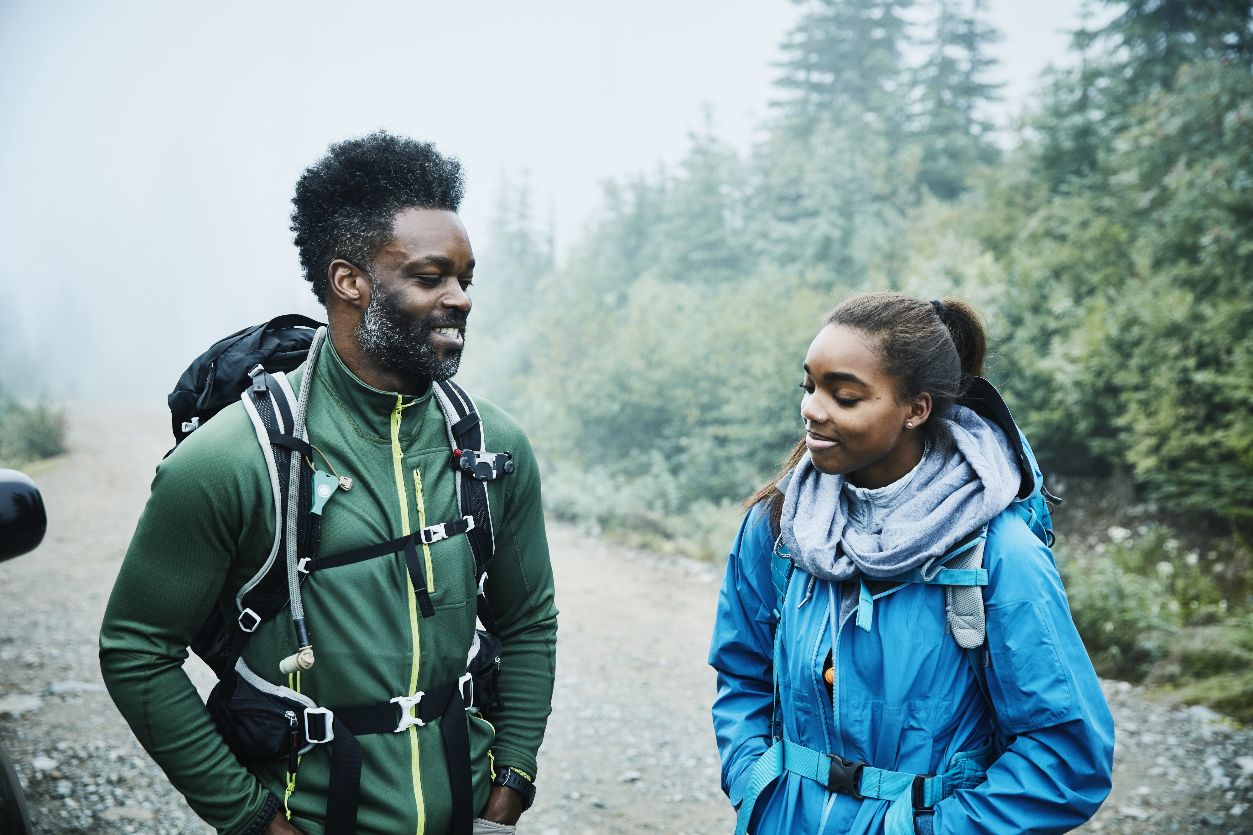 A smiling father and daughter stand and talk next to each other while preparing for early morning hike.