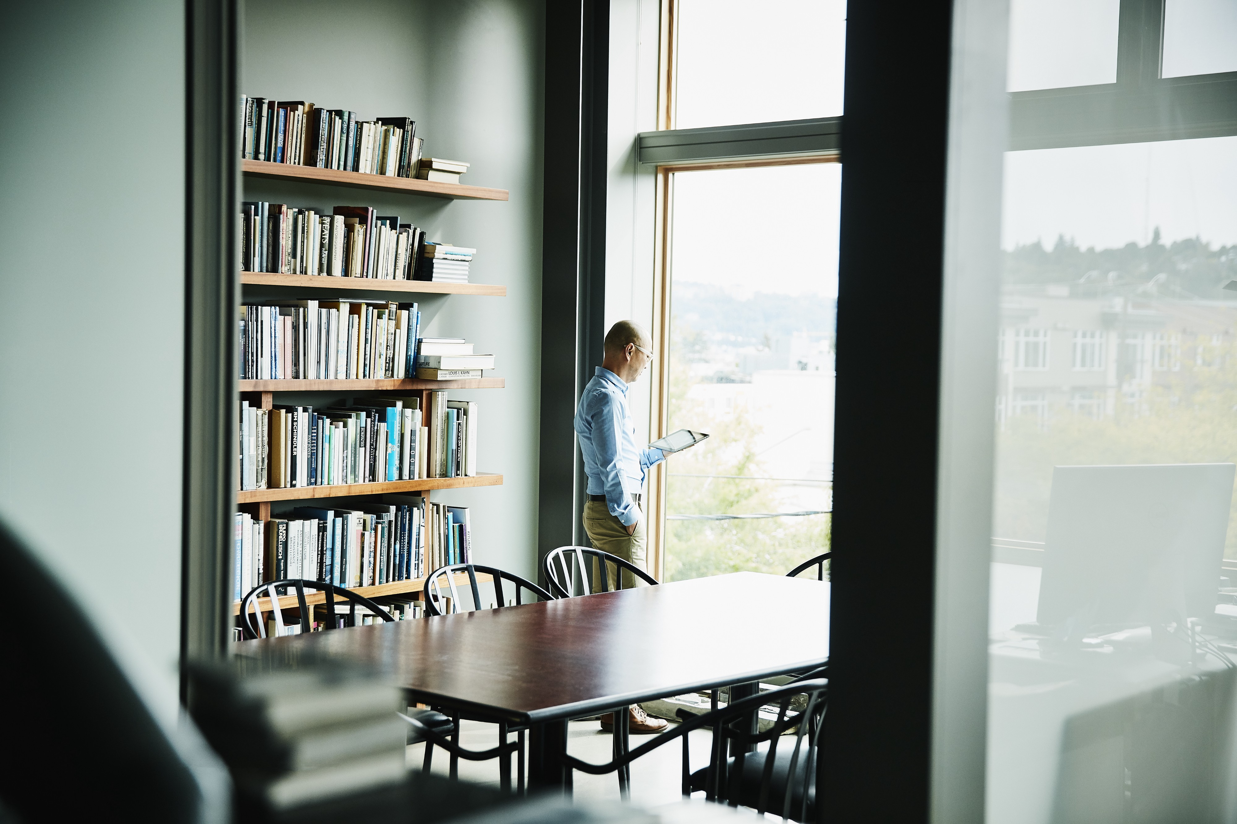 A businessman reading on his digital tablet while standing near a window, next to his filled bookshelves.
