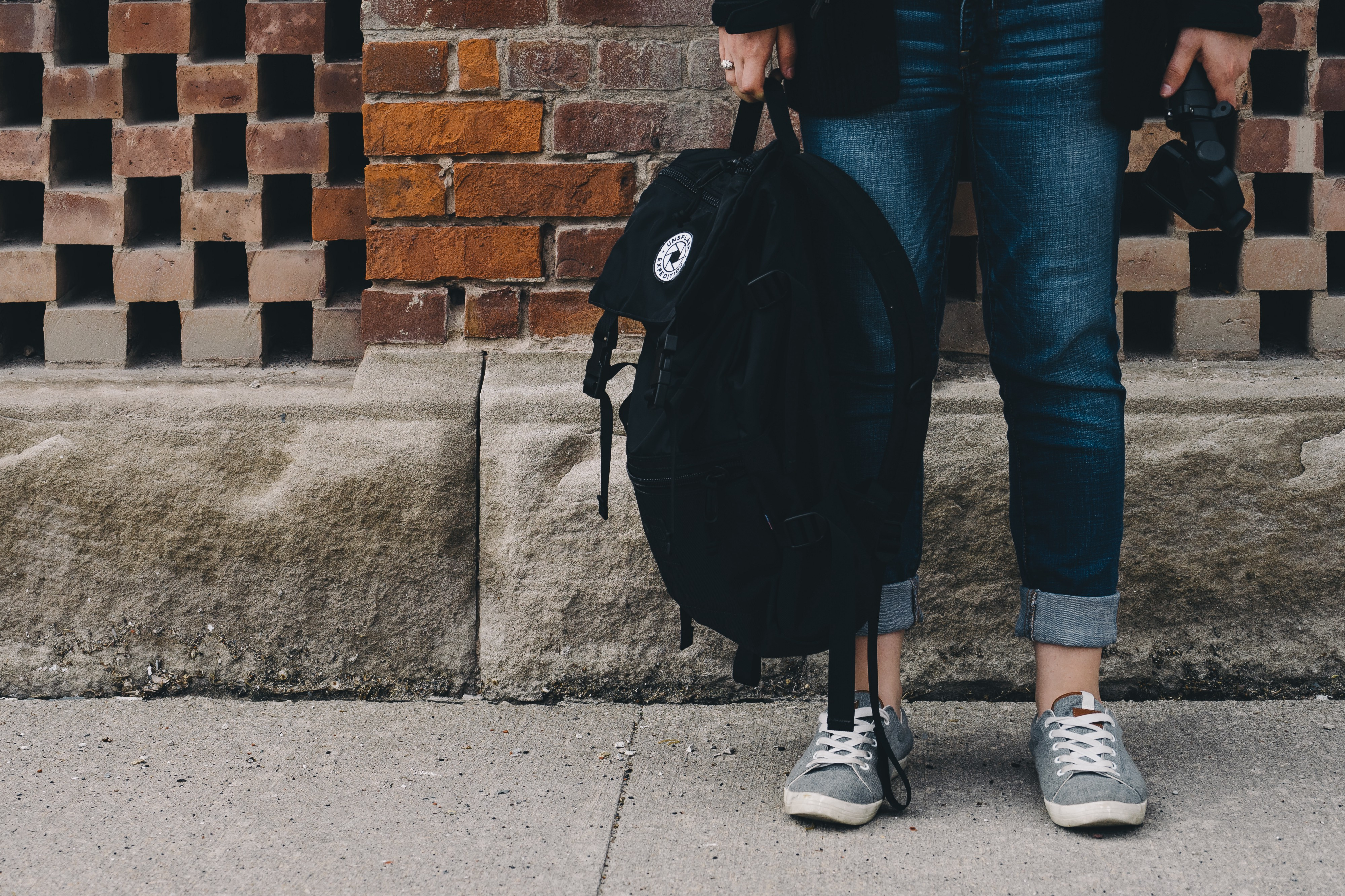 a teenager holding a schoolbag