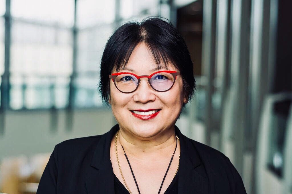 Smiling portrait of East Asian woman with glasses and black suit