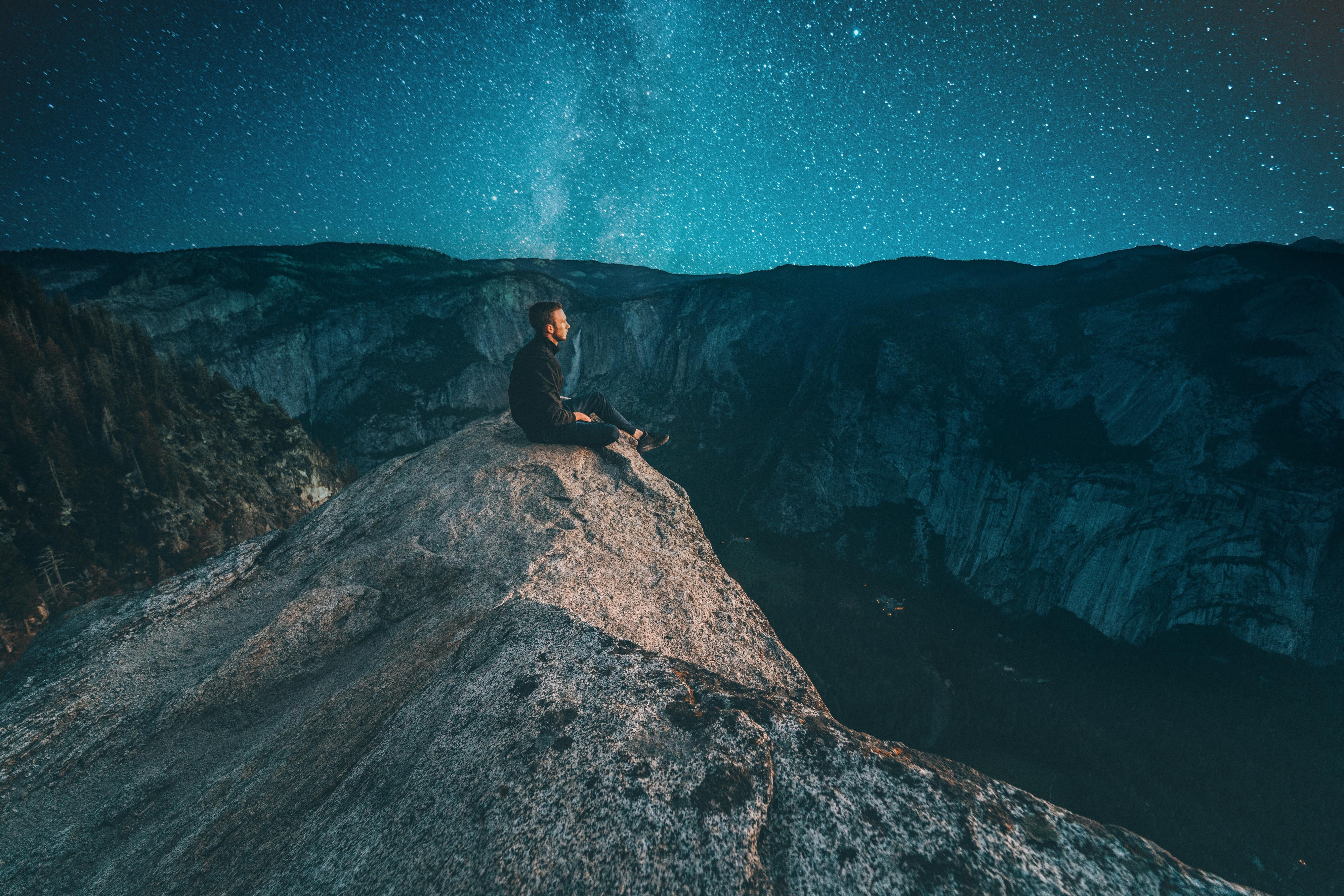 Person sitting on a rock looking out over a mountain range