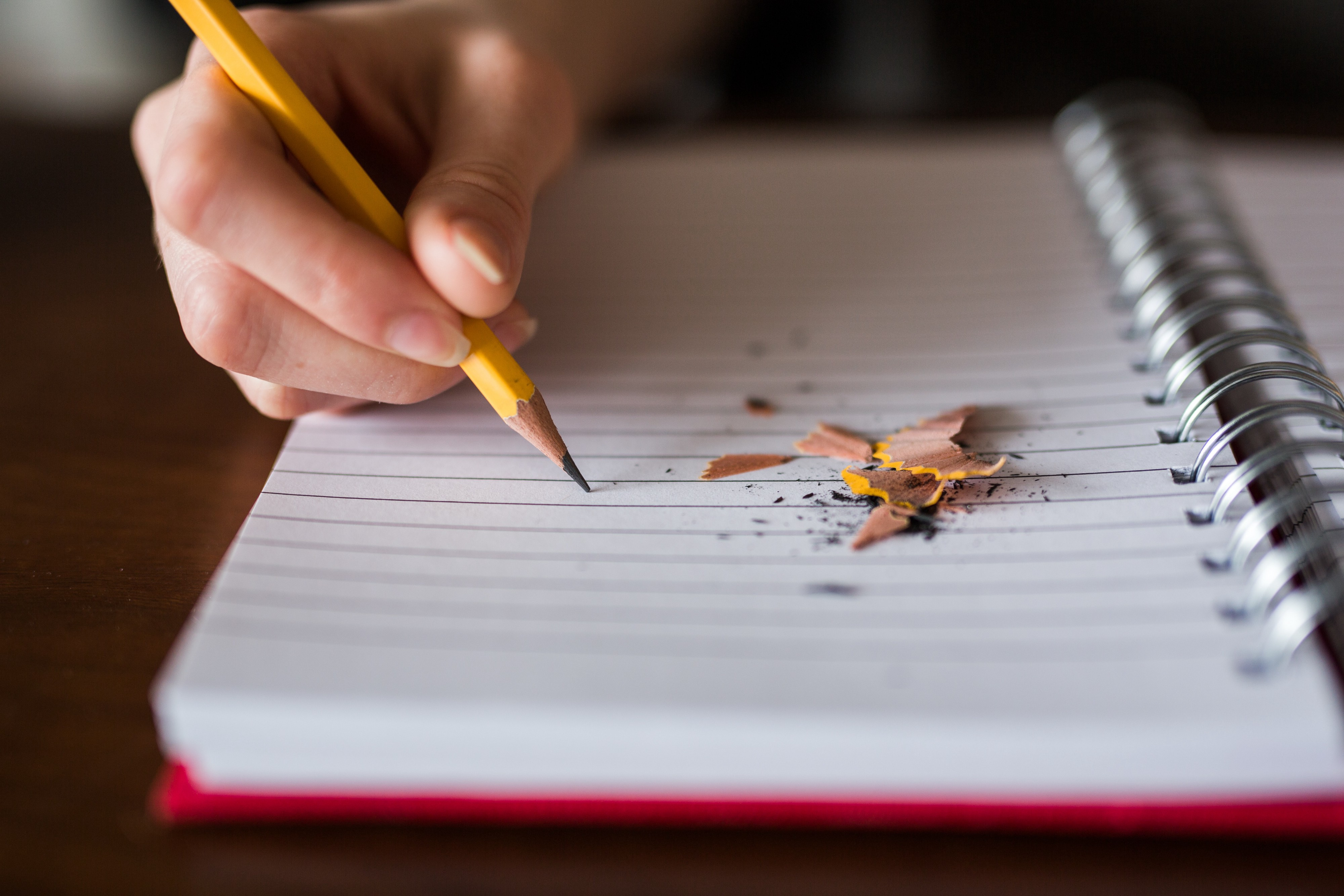 Image of a hand holding a sharpened yellow pencil on a notebook. The sharpening waste is visible on the notebook.