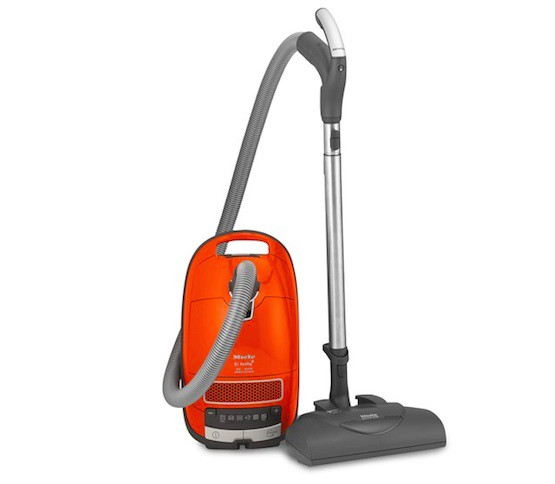 A pet hair vacuum featuring an orange tank with a grey hose and silver and grey attachment