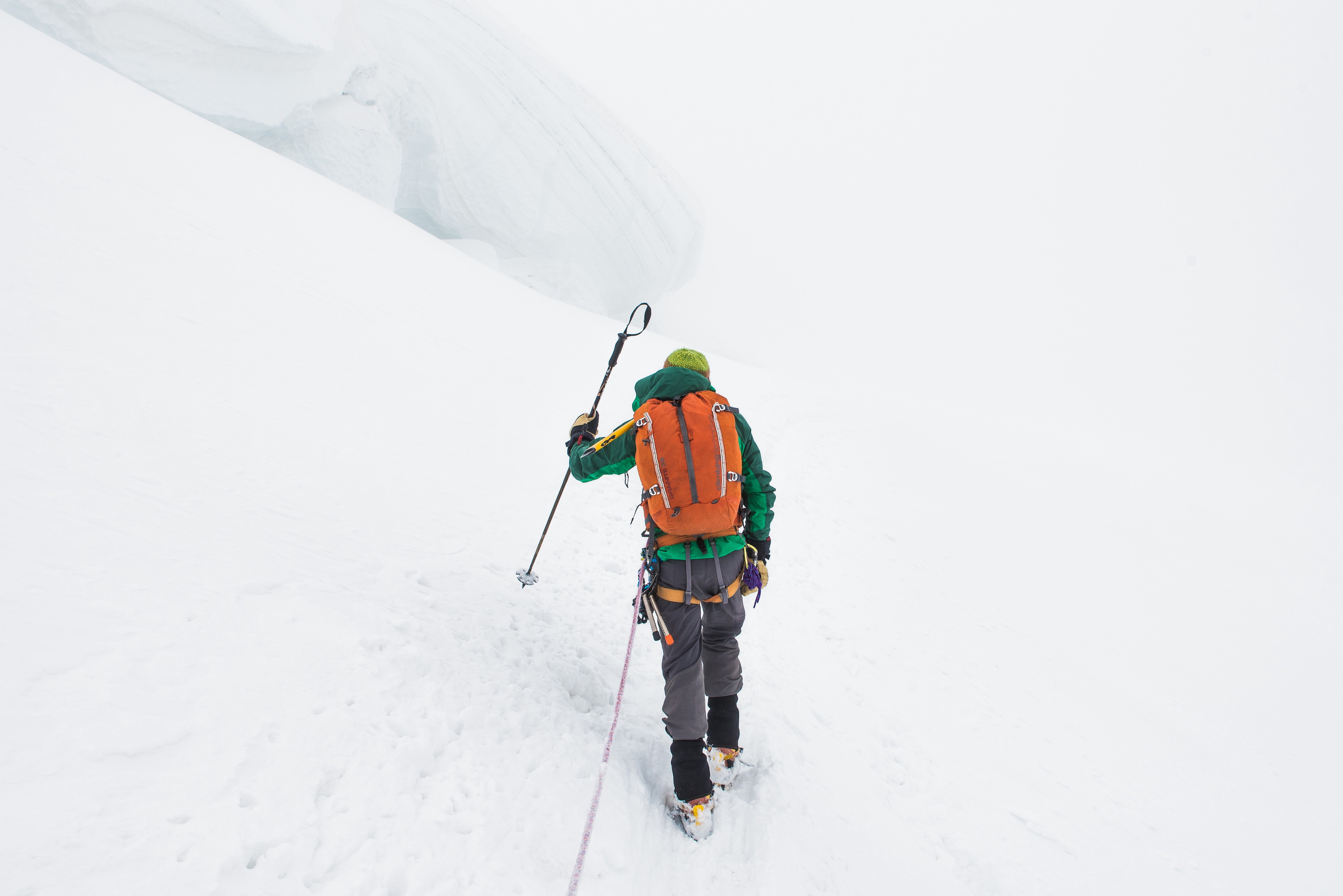 hiker in colorful outfit climbing side of snow-covered mountain