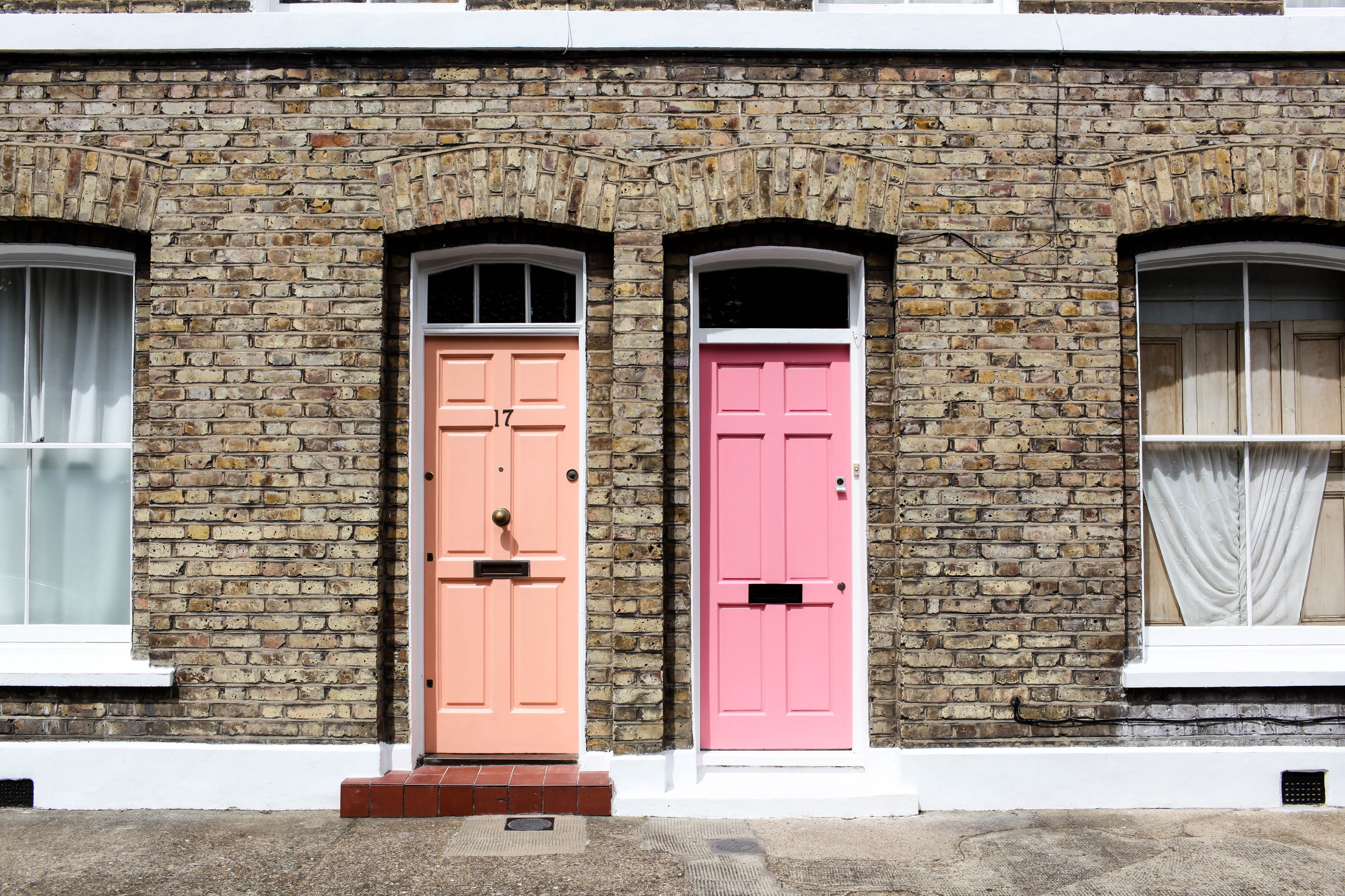 Two doors taken at Columbia Rd. One is beige and the other one is light pink.