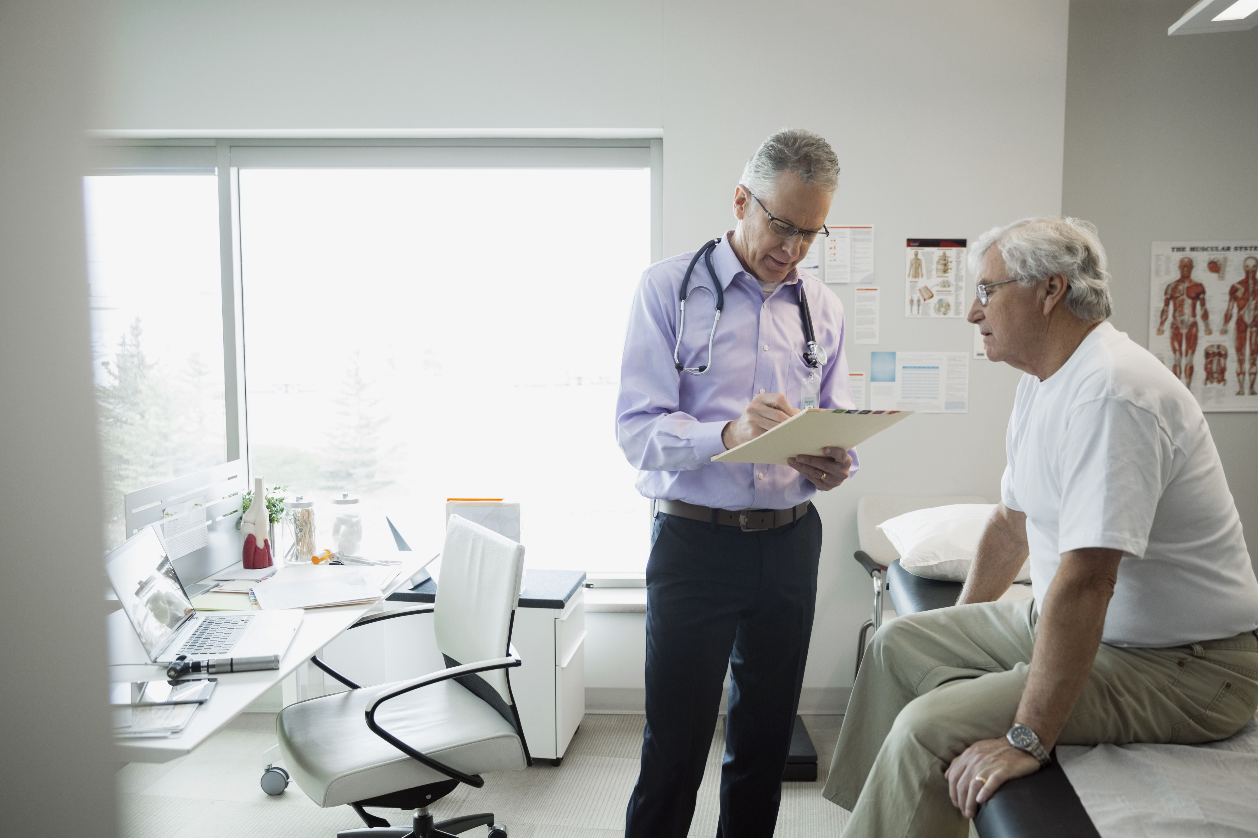 A doctor reviews the medical chart of a senior male patient.