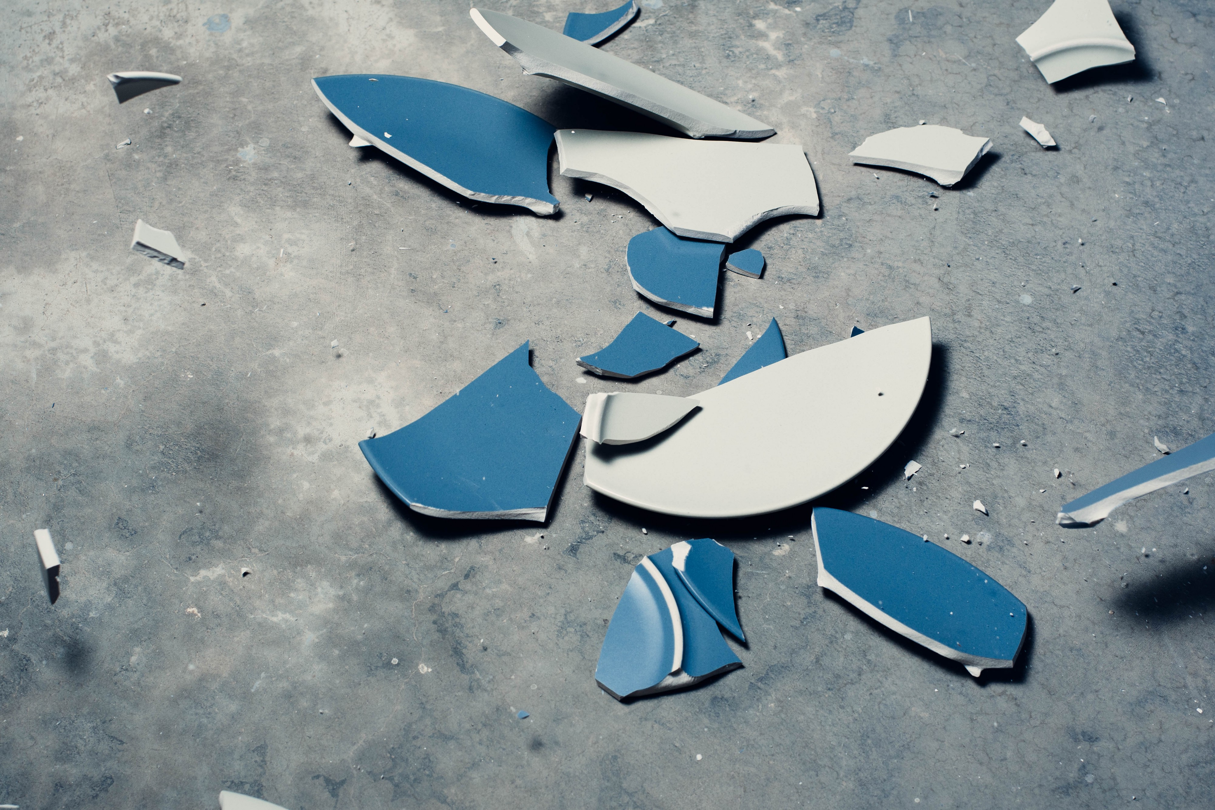 A blue and white plate shattered on a concrete floor.