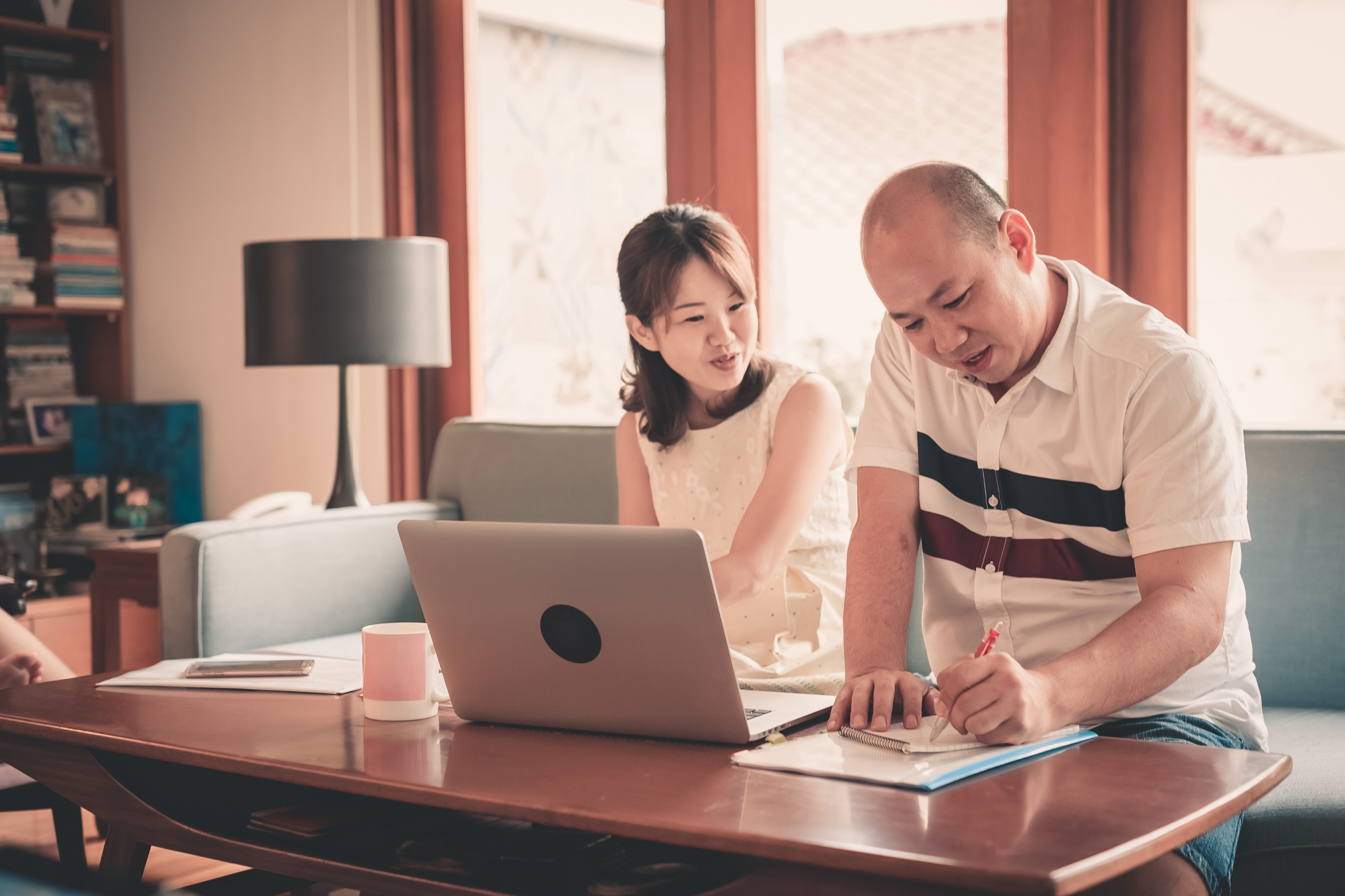 A couple sits on a couch in front of a laptop while one person writes in their notebook.