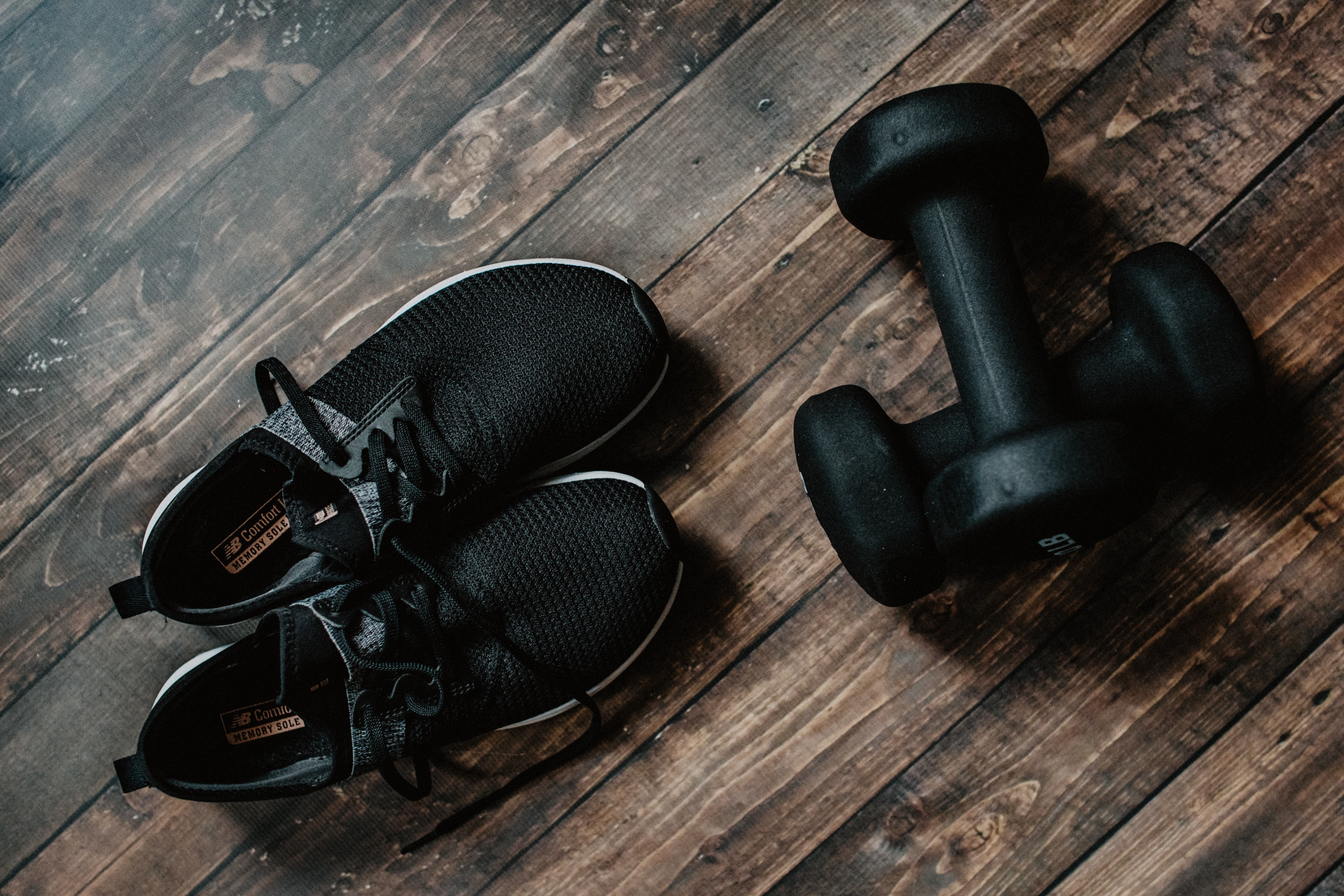 Black sneakers and hand weights on a wooden floor