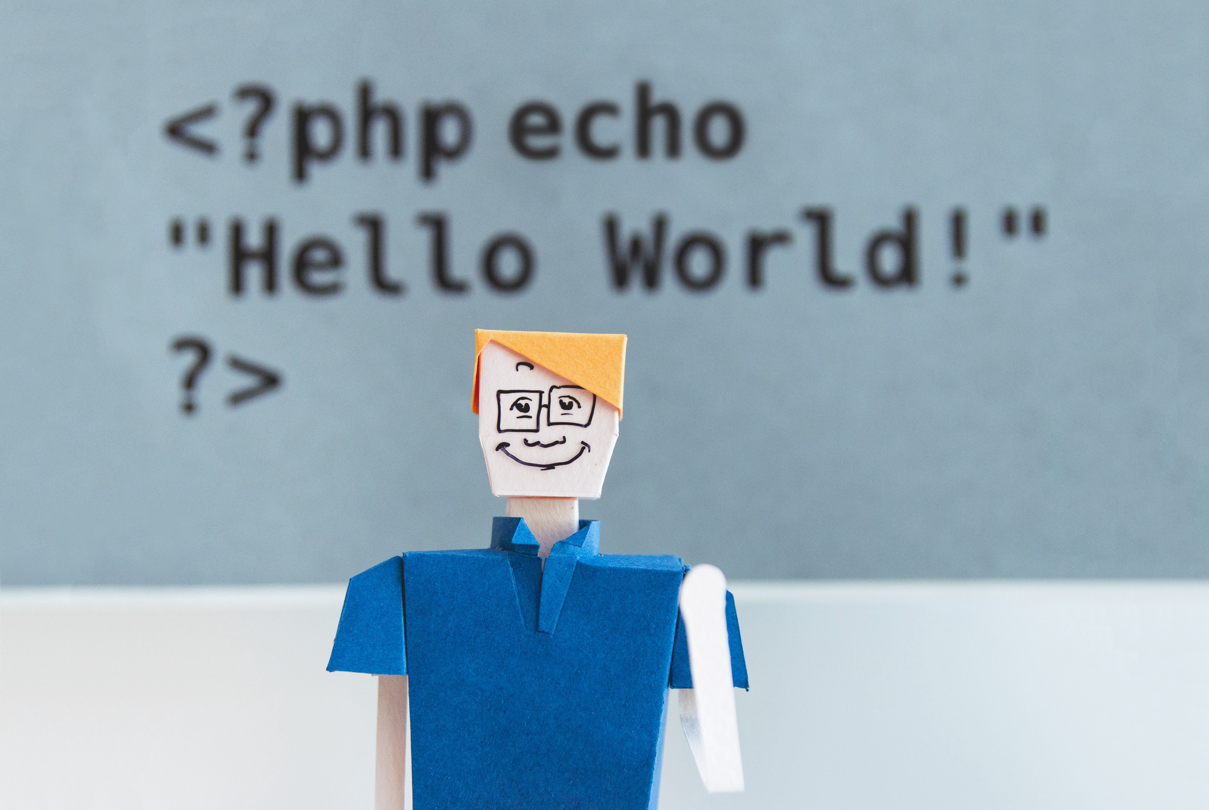 """Paper person with code in the background displaying """"Hello World!"""""""