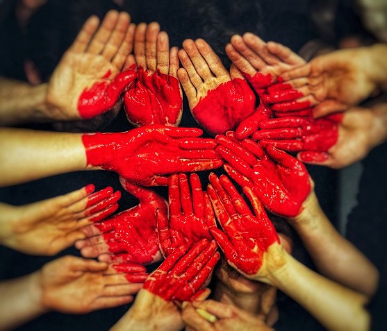 many hands held together with a bright red heart painted across all the hands making up different parts of the heart