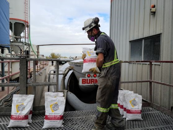 A construction worker is surrounded by Hard-Cem bags and is holding one while preparing to add it to the concrete mix during batching.
