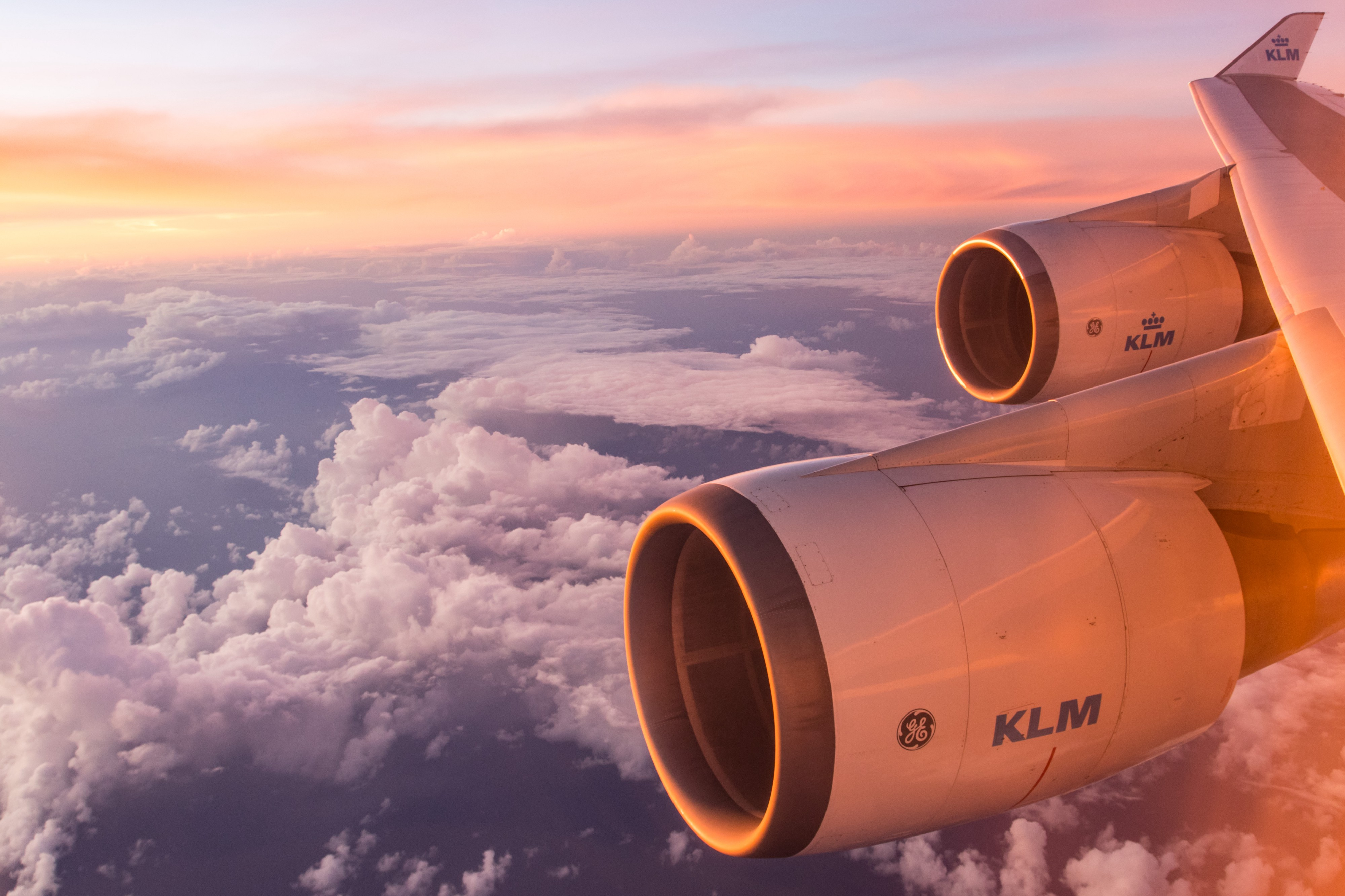 Photo by Emiel Molenaar of clouds and engines outside an airplane window.