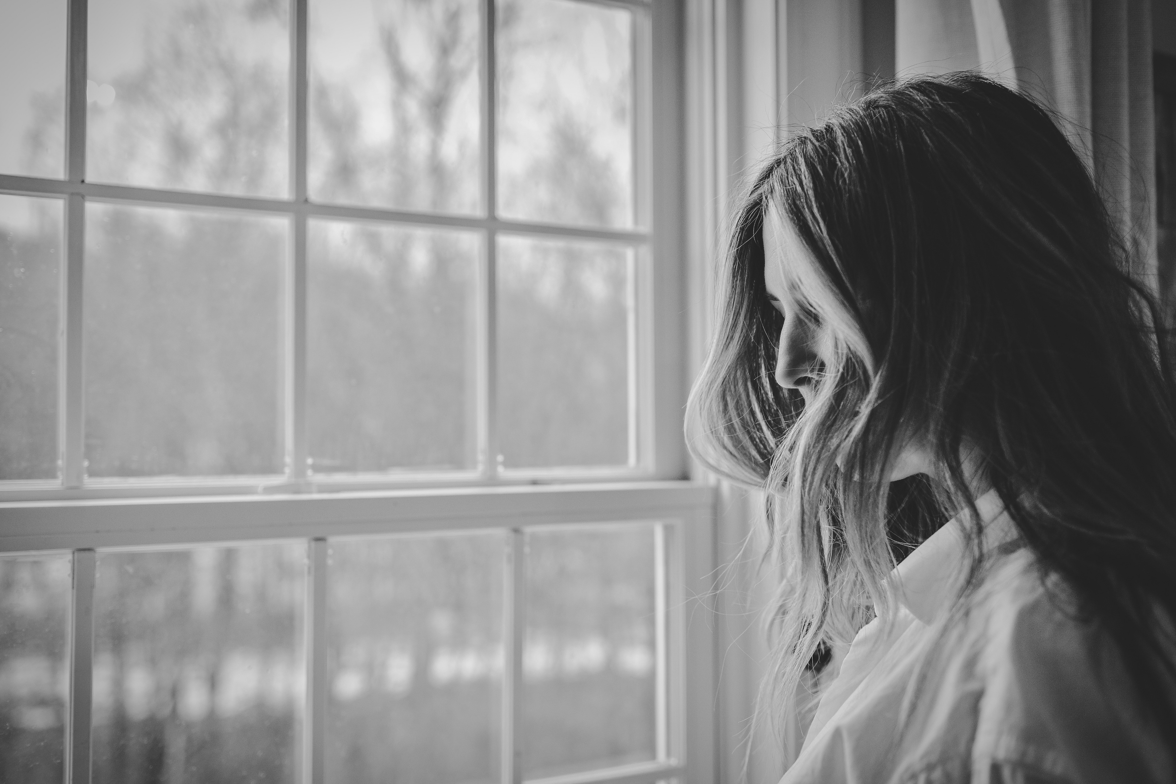 Black and white photo of a woman standing alone looking out a window pane to the faint world outside but not really seeing it