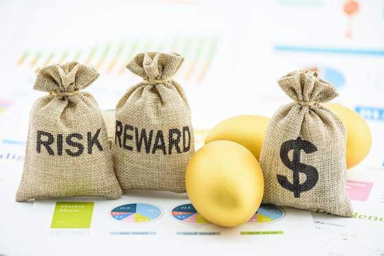 Bags of money on top of financial printouts with Risk, Reward and dollar sign written on them